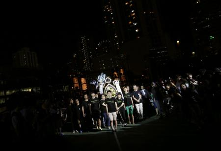 Student protesters walk with wreath during candlelight vigil at Hong Kong's Victoria Park to commemorate those killed during June 4th military crackdown on pro-democracy movement in Beijing