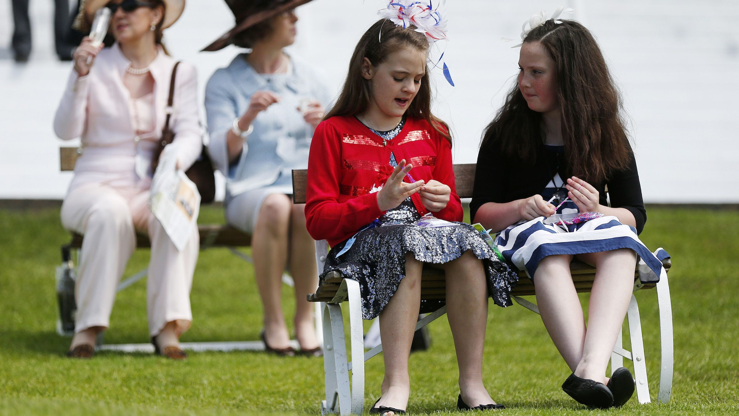 Girls make bracelets while they wait for the start of the first race in the Royal Enclosure at the Epsom Derby Festival in Epsom, southern England June 7, 2014.