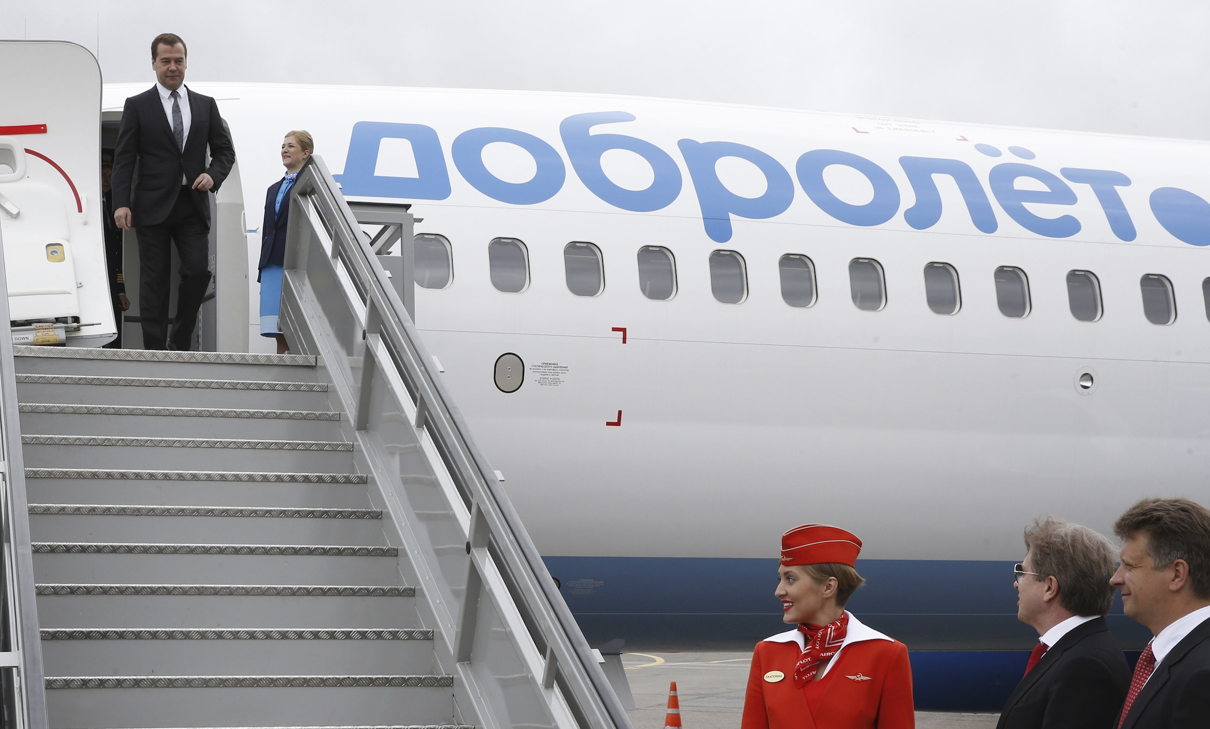Russian Prime Minister Dmitry Medvedev (top) inspects a Boeing 737-800 NG, owned by Dobrolet airline, with Minister of Transport Maxim Sokolov (R, bottom) and Aeroflot CEO and Director General Vitaly Savelyev (2nd R, bottom) seen in the foreground, at Sheremetyevo International Airport outside Moscow, June 10, 2014. Low-cost carrier Dobrolet, Aeroflot's new airline subsidiary, started flights to the Crimean city of Simferopol on Tuesday, according to local media. REUTERS/Dmitry Astakhov/RIA Novosti/Pool (RUSSIA  - Tags: BUSINESS TRANSPORT POLITICS) ATTENTION EDITORS - THIS IMAGE HAS BEEN SUPPLIED BY A THIRD PARTY. IT IS DISTRIBUTED, EXACTLY AS RECEIVED BY REUTERS, AS A SERVICE TO CLIENTS - RTR3T0WW