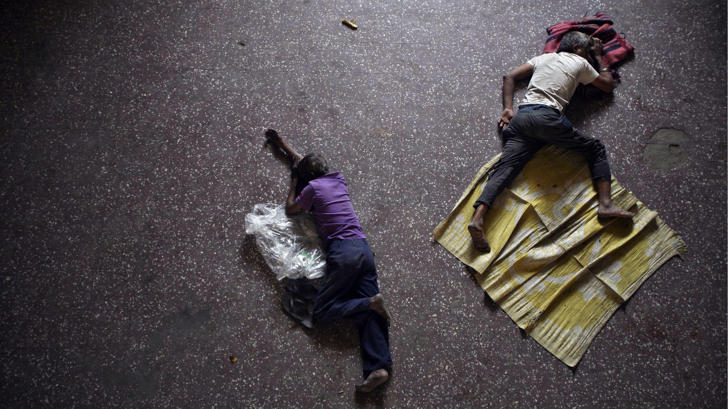 Men sleep on the bus station floor in India