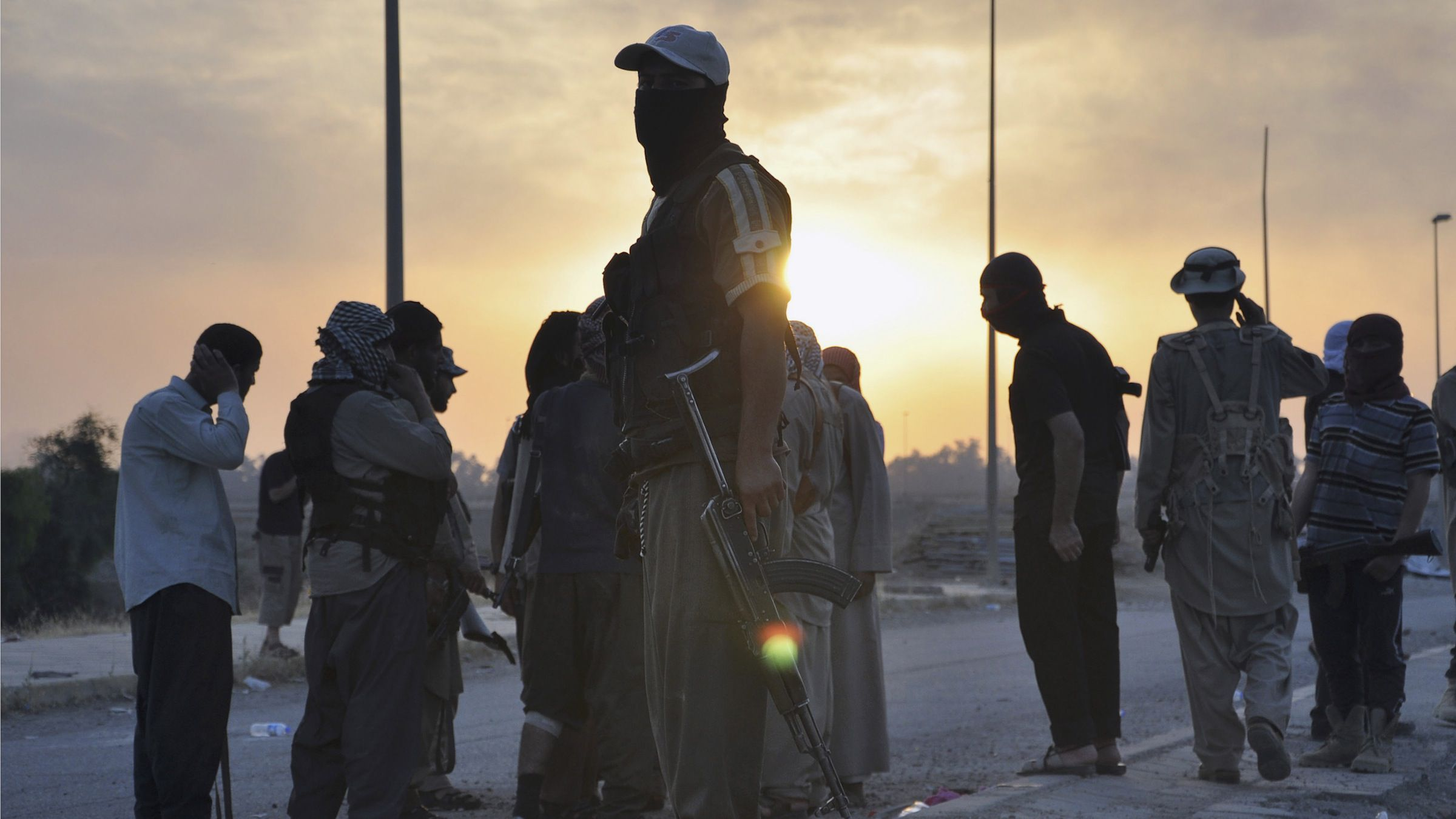 Fighters of the Islamic State of Iraq and the Levant (ISIL) stand guard at a checkpoint in the northern Iraq city of Mosul, June 11, 2014. Since Tuesday, black clad ISIL fighters have seized Iraq's second biggest city Mosul and Tikrit, home town of former dictator Saddam Hussein, as well as other towns and cities north of Baghdad. They continued their lightning advance on Thursday, moving into towns just an hour's drive from the capital. Picture taken June 11, 2014.