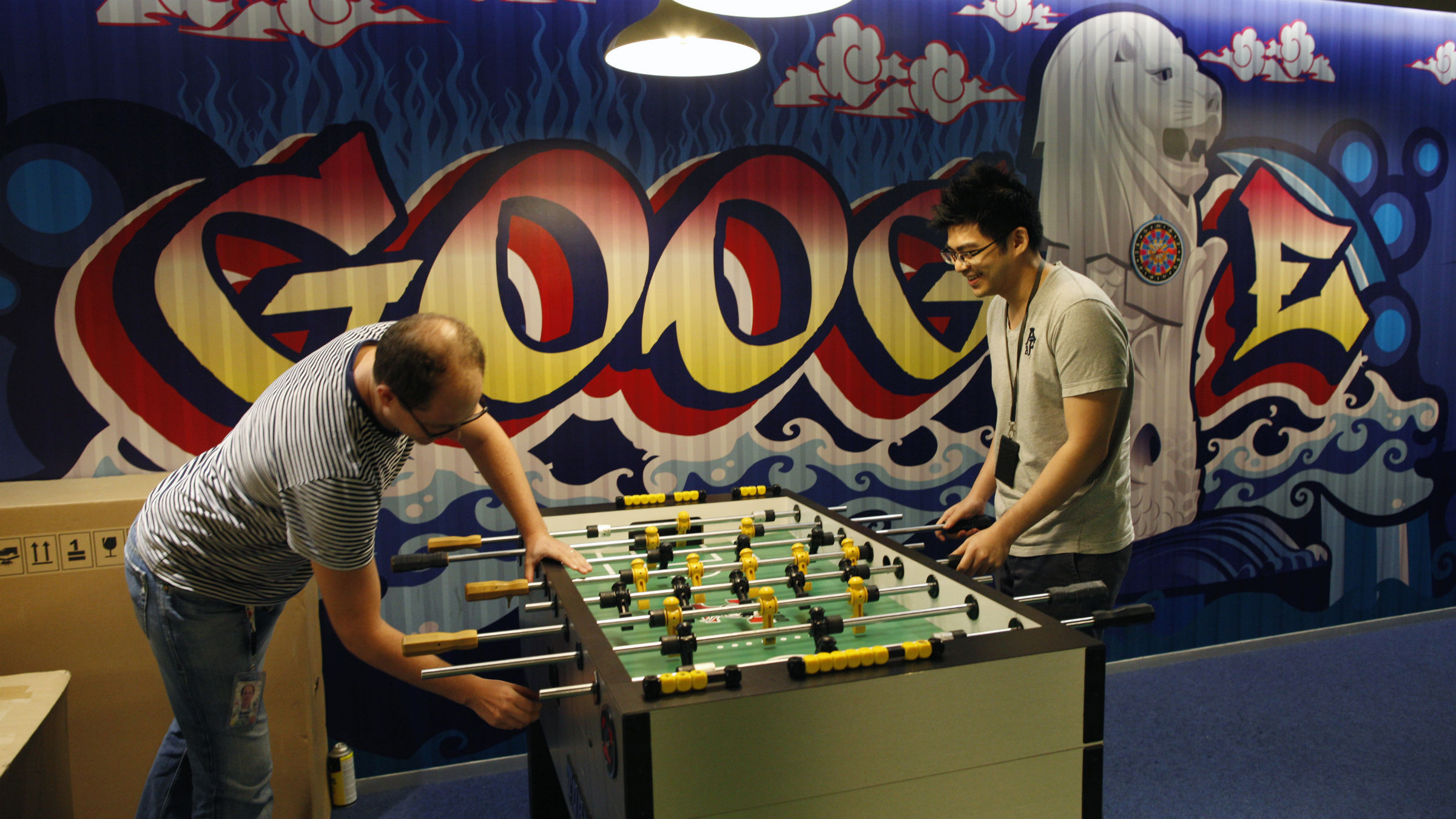 "Google's communications manager Robin Moroney (L) plays table soccer with a Google employee at a recreational area of their Singapore office July 8, 2013. Singapore's move to tighten regulation of news web sites, already under fire from bloggers and human rights groups, has attracted criticism from an unexpected quarter - large internet firms with a big presence in the city-state who say the new rules will hurt the industry. Web giants Facebook Inc, eBay Inc, Google Inc and Yahoo! Inc have said the revised rules ""have negatively impacted Singapore's global image as an open and business-friendly country""."