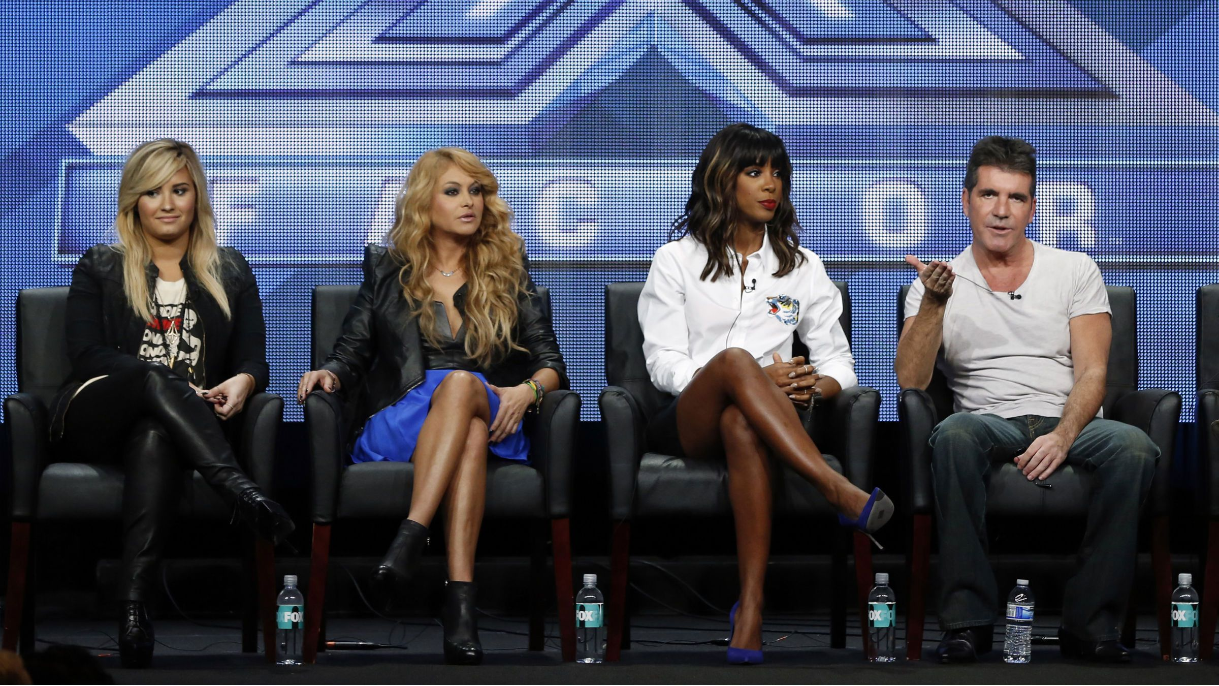 """Judge Simon Cowell speaks next to fellow judges (from L-R) Demi Lovato, Paulina Rubio and Kelly Rowland at a panel for the television series """"The X Factor"""" during the Fox portion of the Television Critics Association Summer press tour in Beverly Hills, California August 1, 2013."""