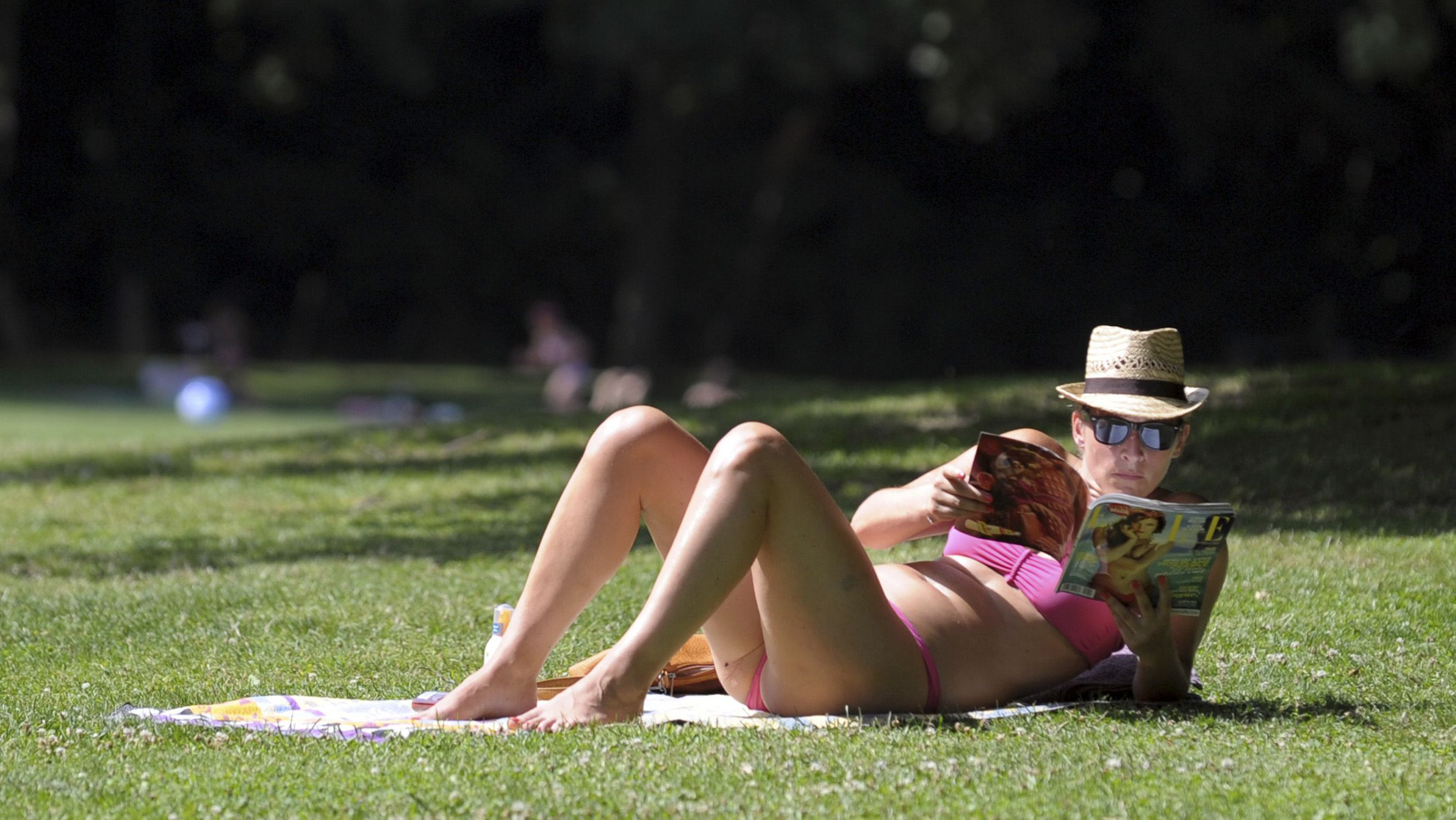 A woman reads Elle magazine at a central park on a warm day in Brussels