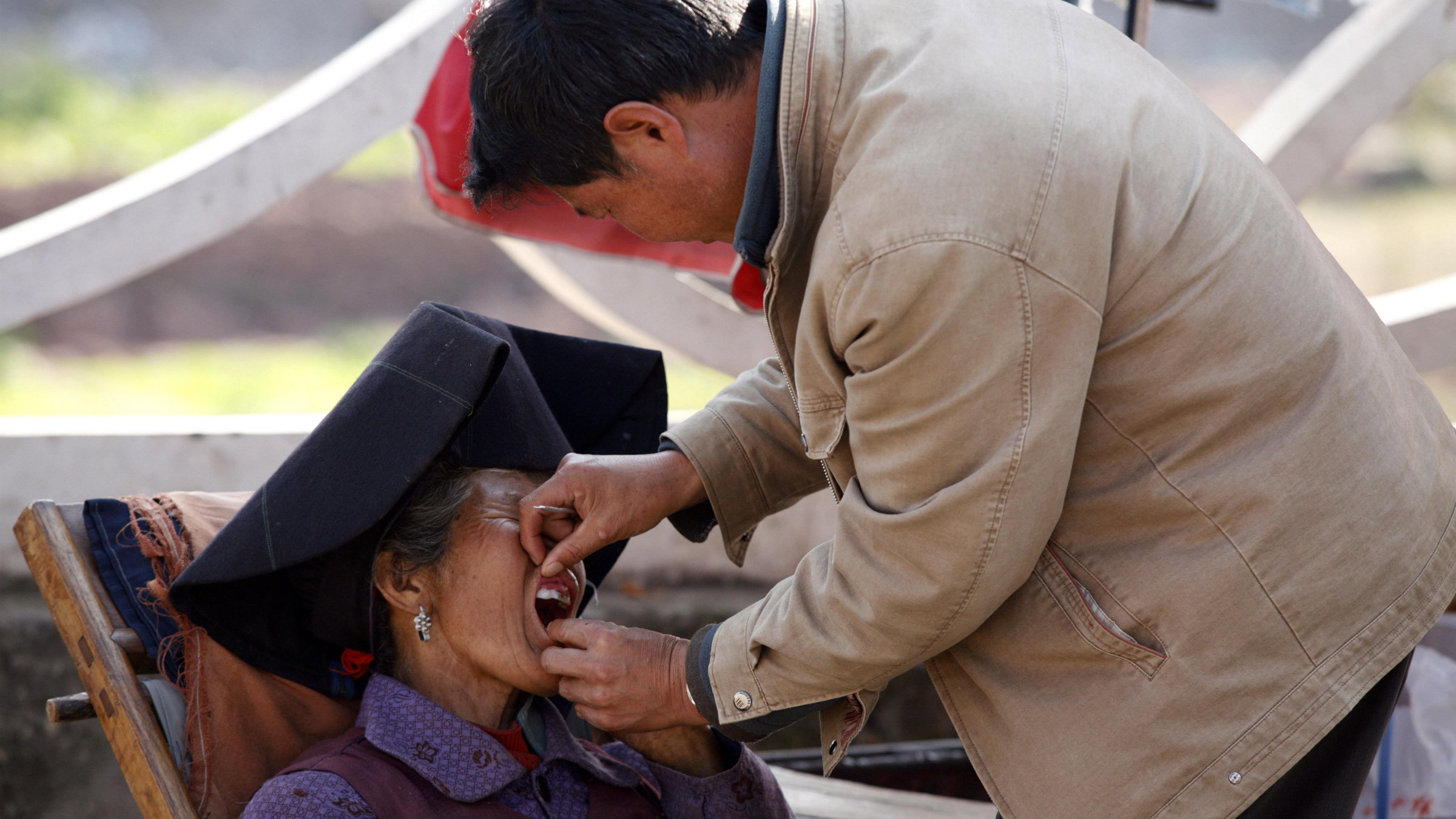 A dentist checks the teeth of a patient in a street market in Xichang, southwest China's Sichuan province.