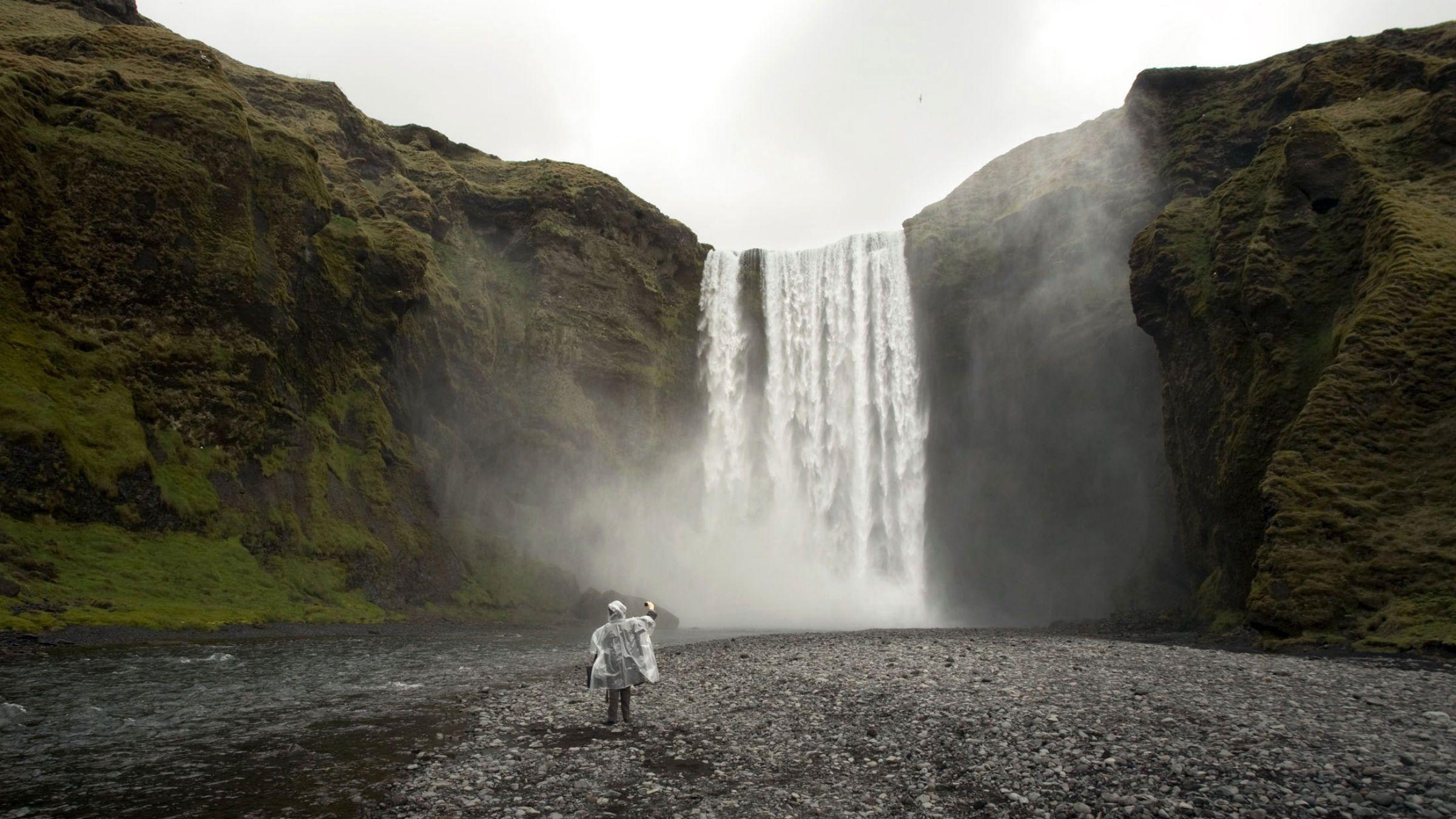A tourist takes photos of Skogafoss waterfall near Skogar on Iceland's southern coast May 10, 2008.