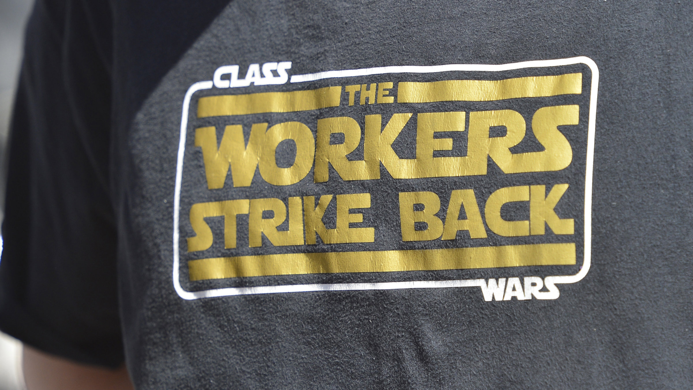 """A t-shirt reads """"Class Wars: The Workers Strike Back"""""""