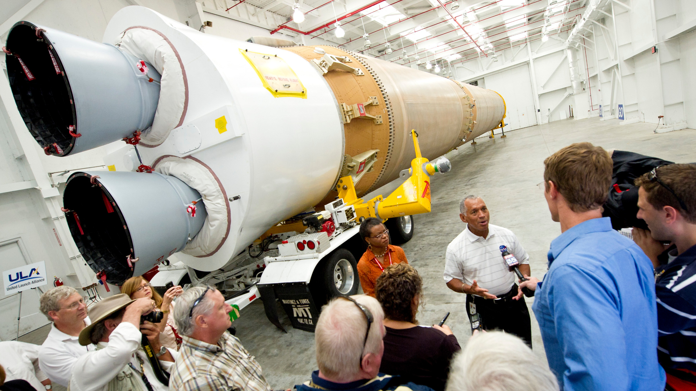 NASA Administrator Charles Bolden, stands in front of the Atlas V first stage booster while taking questions from the media, Wednesday, Sept. 7, 2011, at the Cape Canaveral Air Force Station in Cape Canaveral, Fla. The booster will help send NASA's Mars Science Laboratory Curiosity rover to Mars later this year.