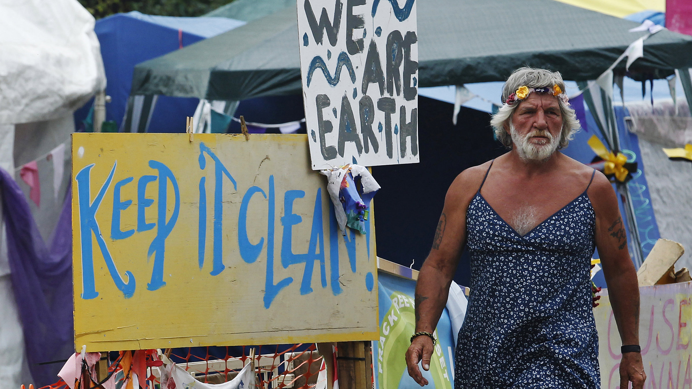 A man wearing a dress walks past signs at the protest camp in front of a drill site run by Cuadrilla Resources, in the village of Balcombe in southern England September 3, 2013. Caudrilla Resources's site in the village of Balcombe in rural West Sussex has become a focal point for protesters who oppose fracking, a technique the company has pioneered in the search for shale gas in Britain.