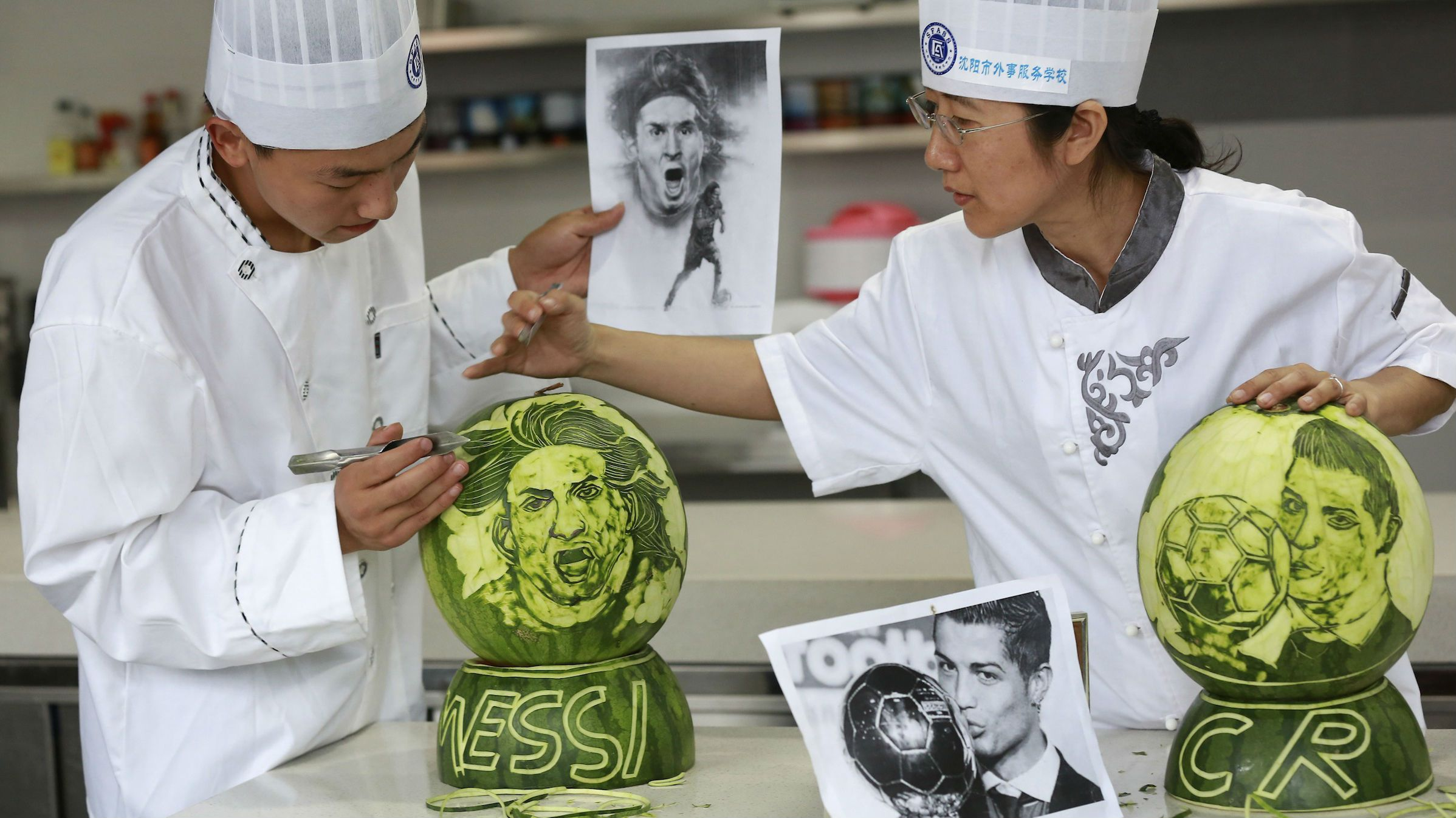 A culinary teacher (R) and a student carve images of Argentine soccer player Lionel Messi and Portugal's Cristiano Ronaldo on watermelons, ahead of the 2014 World Cup in Brazil, in Shenyang, Liaoning province, June 11, 2014. REUTERS/Stringer