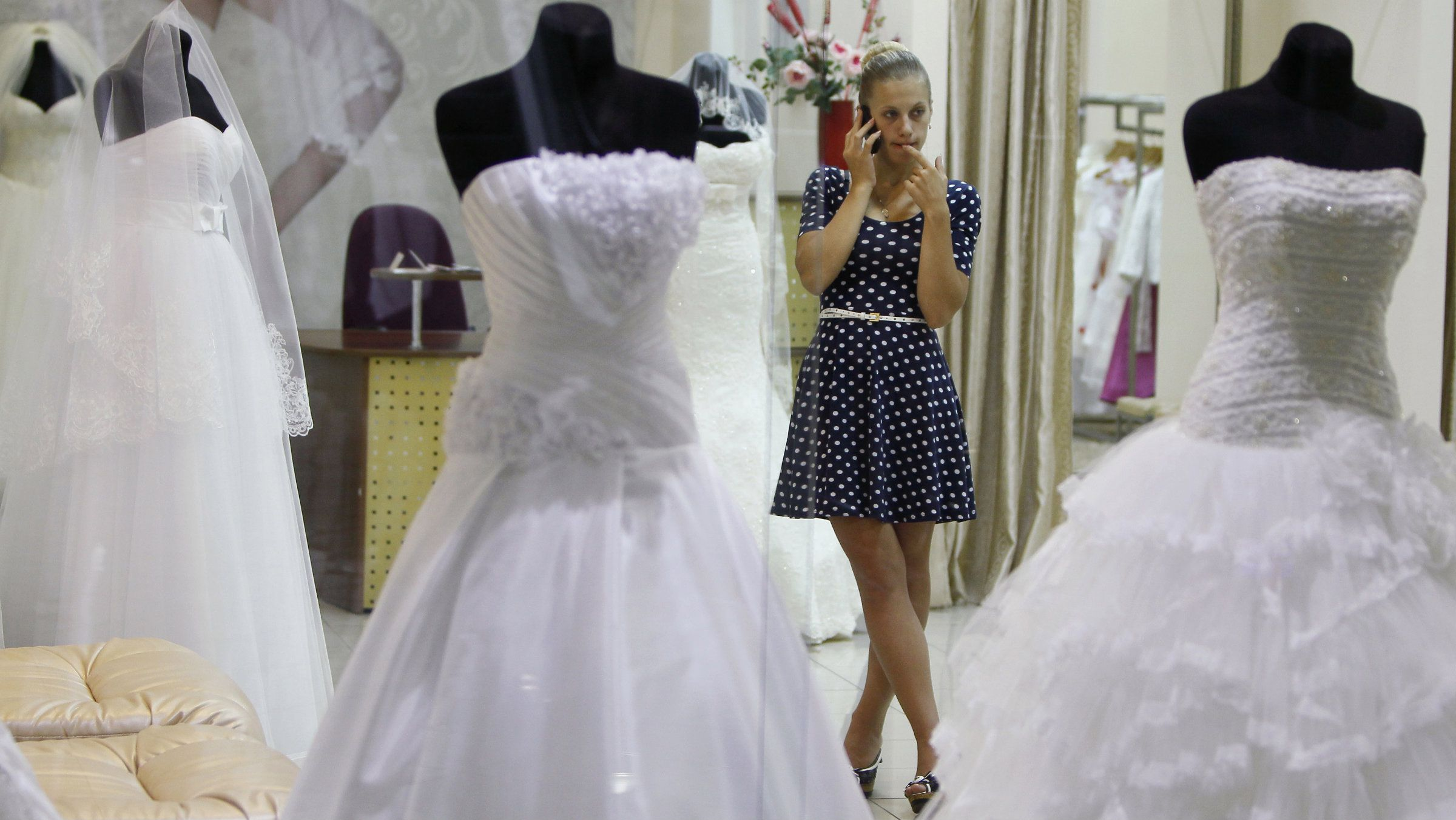 Woman on phone in a bridal gown store.