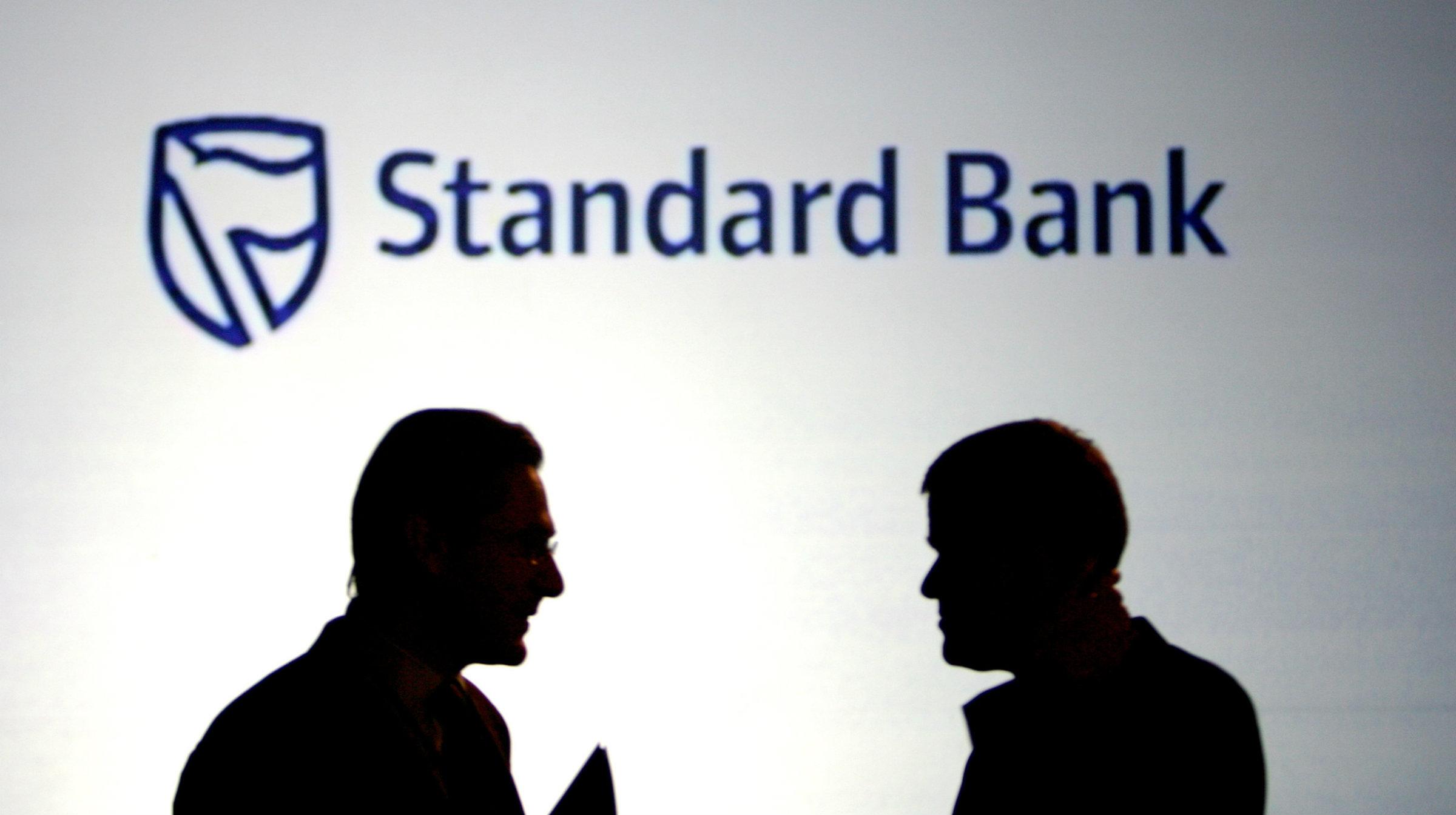 standard bank sign with men in the front in shaadow