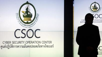 A man is silhouetted against a screen at the cyber security operation centre in Bangkok