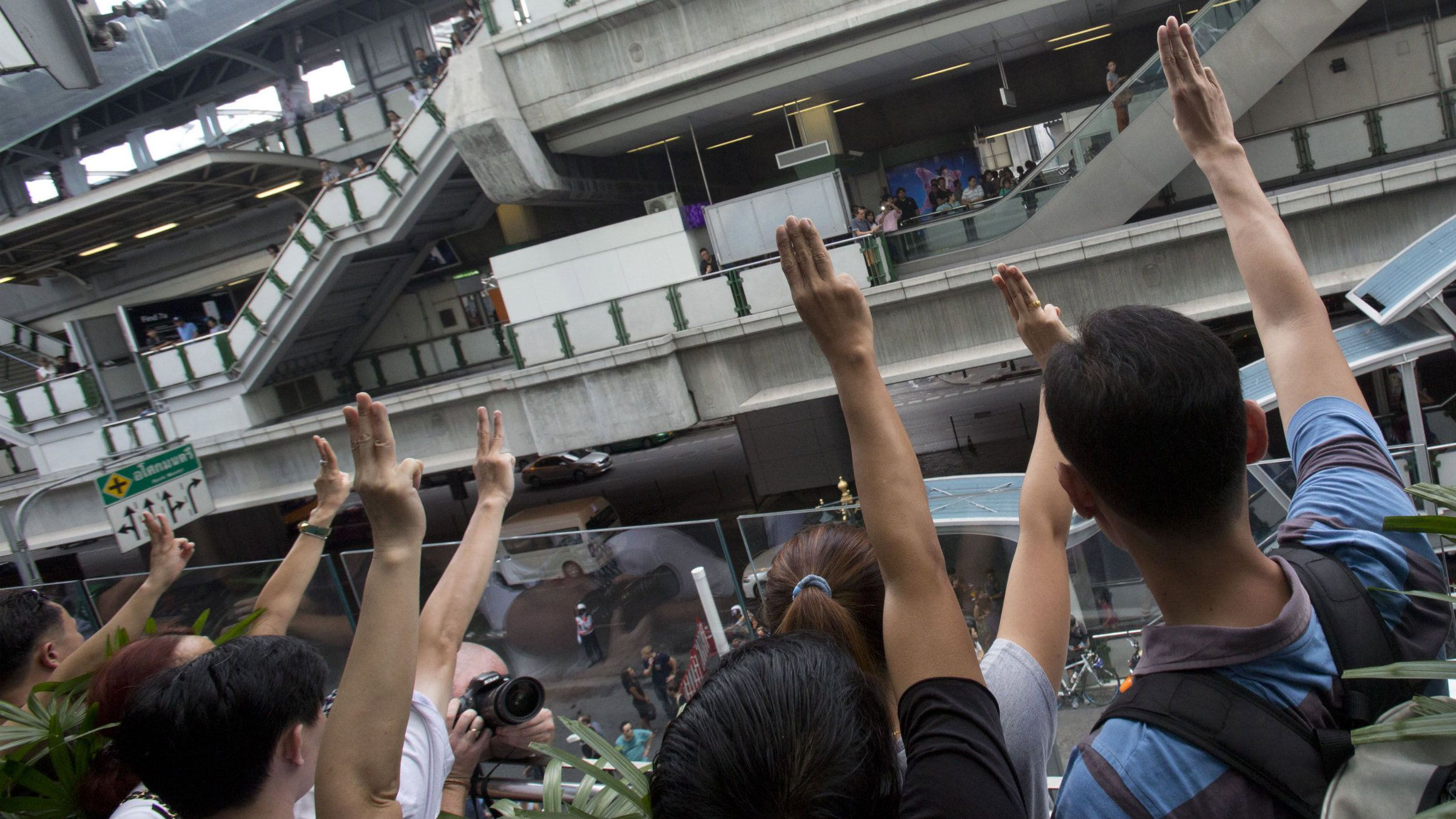 """Protesters raise three fingers, representing liberty, brotherhood and equality, during an anti-coup demonstration in Bangkok, Thailand Sunday, June 1, 2014. Hundreds of demonstrators shouting """"Freedom!"""" and """"Democracy!"""" gathered Sunday near a major shopping mall in downtown Bangkok to denounce the country's May 22 coup despite a lockdown by soldiers of some of the city's major intersections. (AP Photo/Sakchai Lalit)"""
