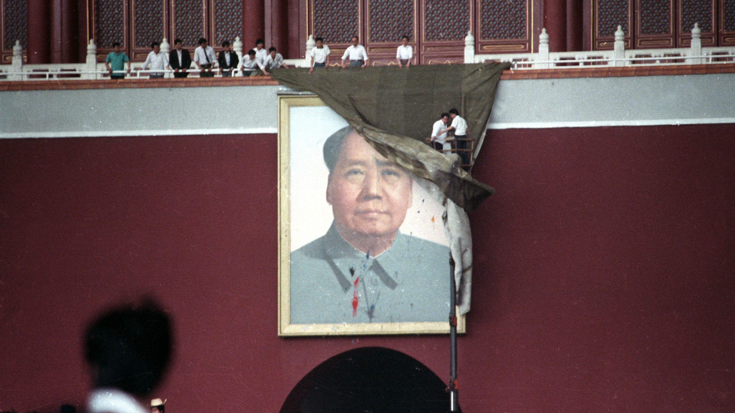 Workmen try to drape the portrait of Mao Tse-tung in Beijing's Tiananmen Square after it was pelted with paint in this May 23, 1989.