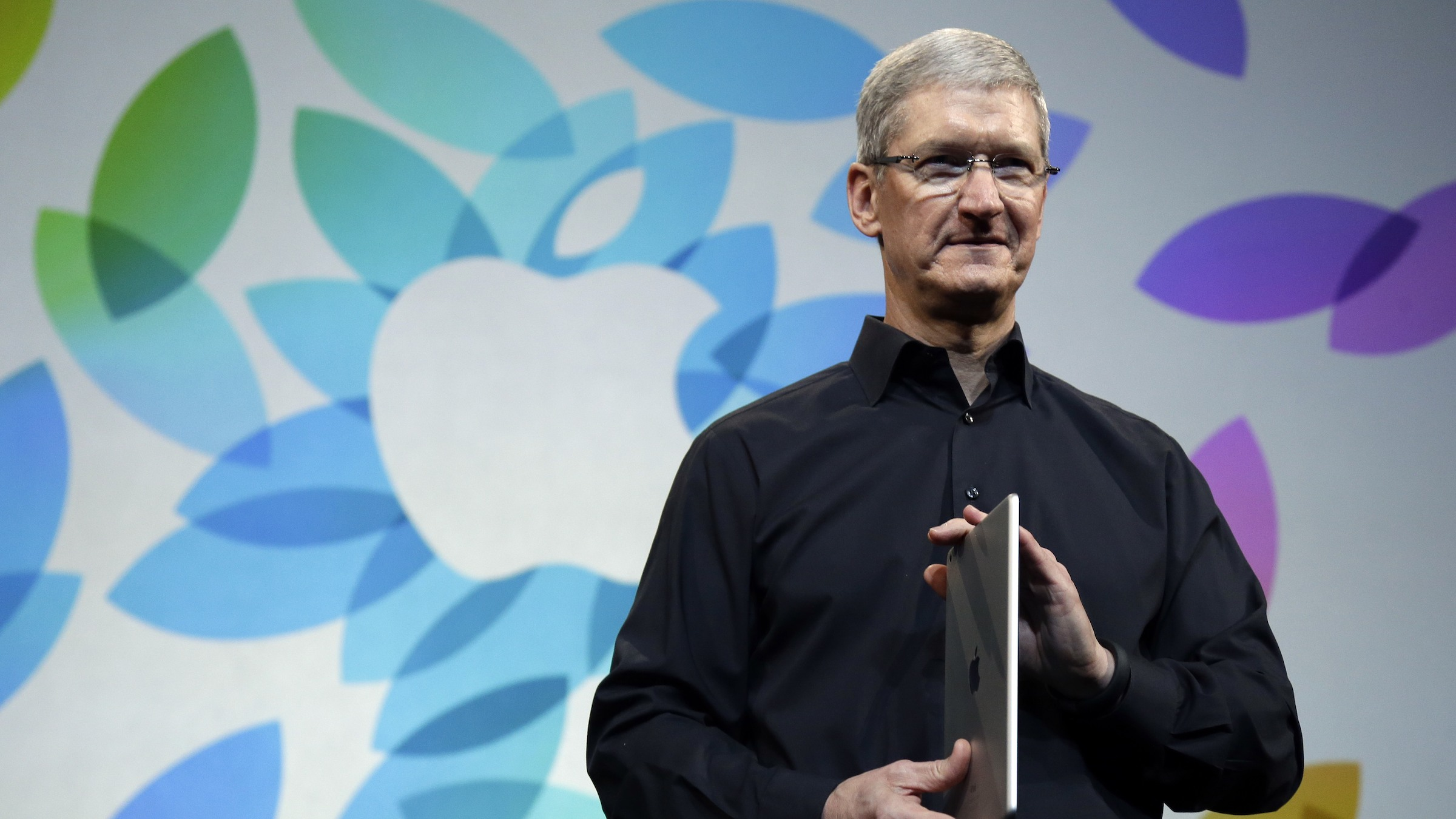 Apple CEO Tim Cook holds an iPad Air