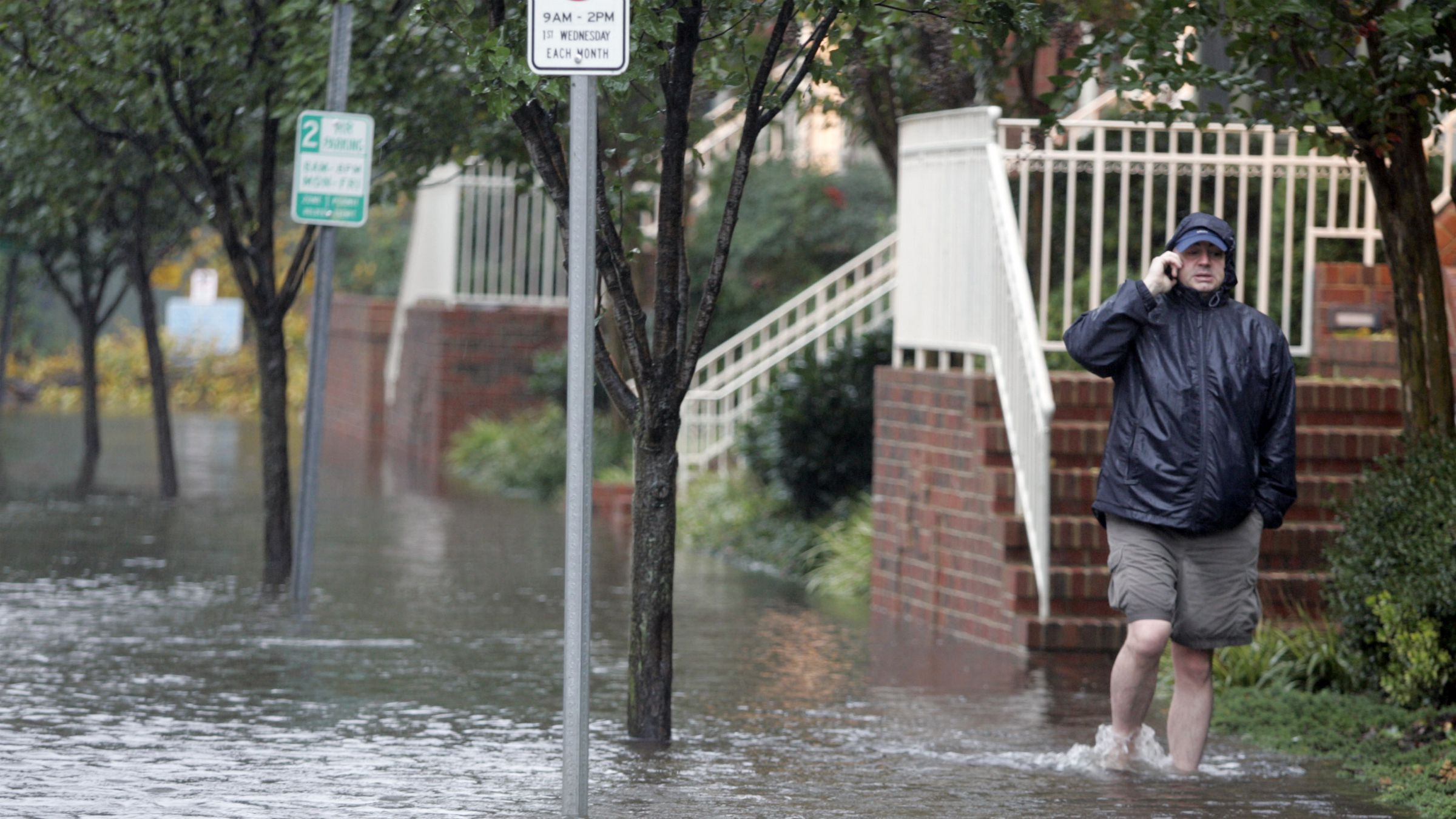 sea level rise storm surge flooding climate change global warming virginia A resident talks on his cell as he walks through a flooded street in Norfolk, Va., Friday, Nov. 13, 2009. The area has been hit by remnants of tropical storm Ida. (AP Photo/Steve Helber