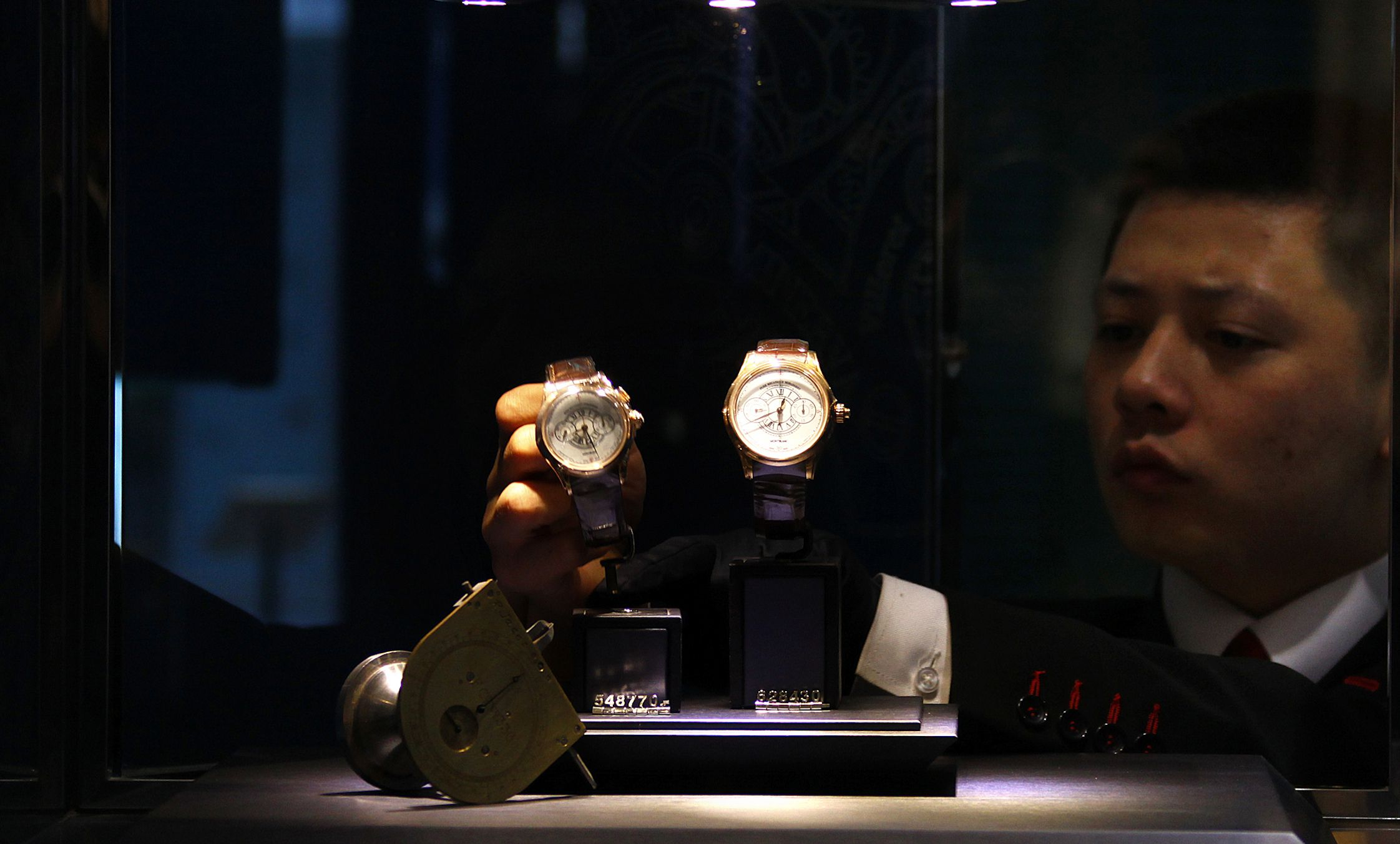 A worker adjusts a display of Mont Blanc watches at the luxury-goods company's new store in Beijing January 5, 2012. High-end penmaker Montblanc has opened its largest store in China to capitalise on the surging growth of Chinese luxury-goods consumers, who are expected to account for most of the world's luxury purchases in eight years. The four-storey store is in a recently developed area of Beijing's trendy Sanlitun district - which includes Armani, Longchamp, Rolex and other luxury boutiques - and is meant to appeal to China's growing middle class who are increasingly obsessed with the latest and most exclusive fashions after decades in which the Communist Party frowned on fancy clothes, accessories and make-up. Picture taken January 5, 2012.      REUTERS/David Gray (CHINA - Tags: BUSINESS EMPLOYMENT SOCIETY) - RTR2WCUG