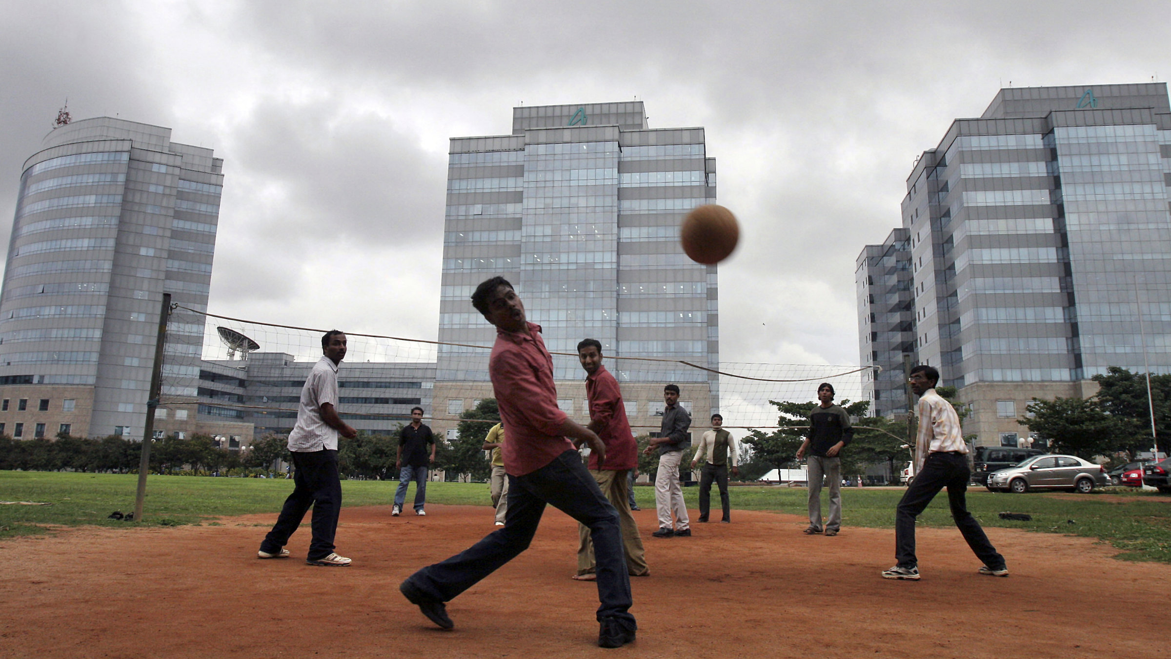 Indian workers play volleyball outside skyscrapers in Bangalore.