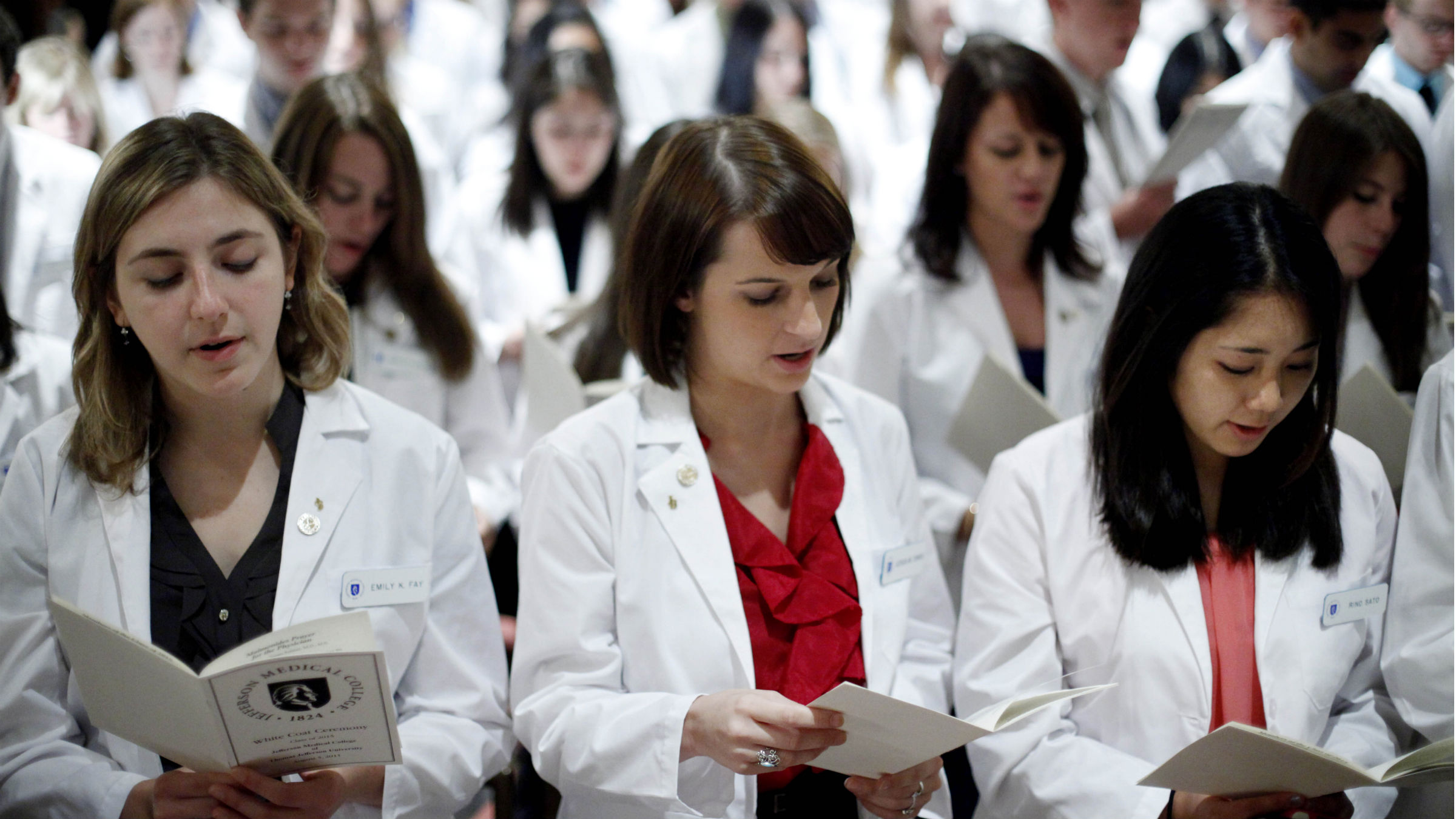 Thomas Jefferson University's Jefferson Medical College first-year students from left, Emily K. Fay, Jessica M. Torres, and Rino Sato take the Hippocratic Oath during the annual White Coat Ceremony, Friday, Aug. 5, 2011, in Philadelphia. The ceremony symbolizes the clinical beginning of the students' medical educations.