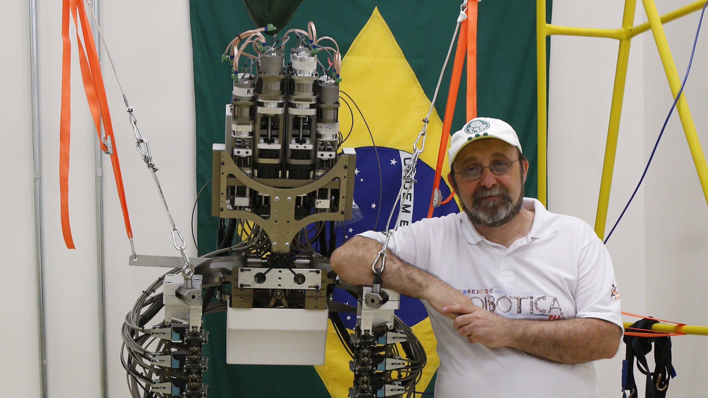 """Brazilian neuroscientist Miguel Nicolelis poses with a robotic exoskeleton in Sao Paulo May 21, 2014. Nicolelis is leading """"The Walk Again Project"""", where the mechanical exoskeleton is able to support a paralyzed person's lower body and responds to wireless commands that come from electrodes placed on the person's scalp or within the brain. The robotic exoskeleton could allow a paraplegic to deliver the first kick of the World Cup in Brazil next month, as part of a project to showcase technology aimed at overcoming paralysis. Picture taken May 21, 2014. REUTERS/Paulo Whitaker (BRAZIL - Tags: SPORT SOCCER WORLD CUP SCIENCE TECHNOLOGY)"""