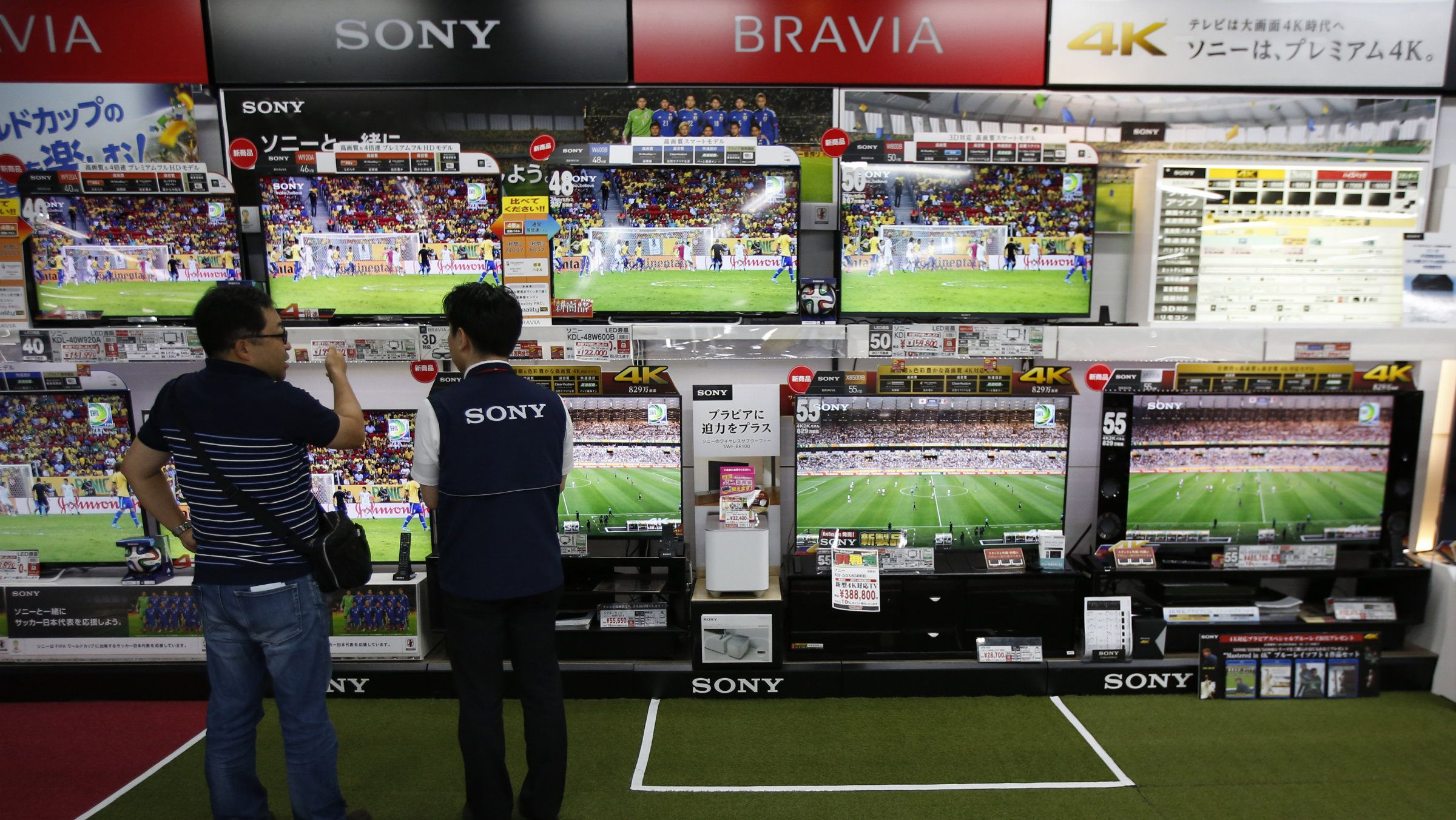 People stand in front of a bank of television screens showing the World Cup.