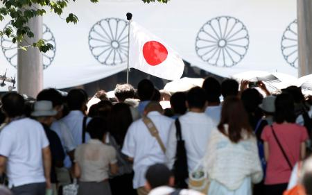 A Japan's national flag flutters among visitors at the Yasukuni Shrine in Tokyo August 15, 2014, on the 69th anniversary of Japan's surrender in World War Two. Japanese Prime Minister Shinzo Abe on Friday sent a ritual offering to the Tokyo shrine to war dead but did not join senior government officials in a visit, a decision meant to avoid inflaming ties with Beijing as he seeks a Sino-Japanese summit.