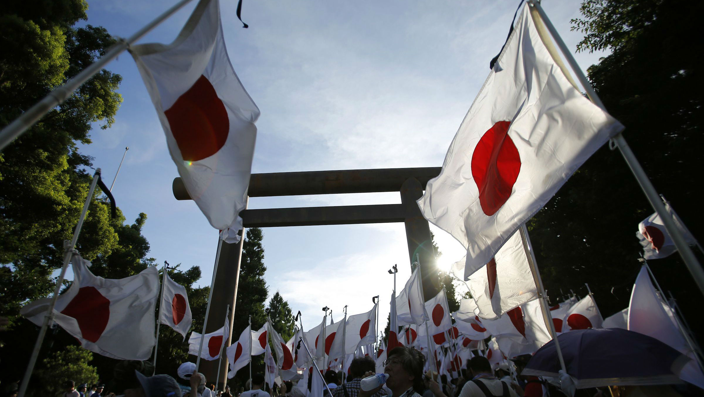 "Members of nationalist movement ""Ganbare Nippon"" holding Japanese national flags gather under the huge Torii gate at the Yasukuni shrine while paying tribute to the war dead in Tokyo August 15, 2014,"