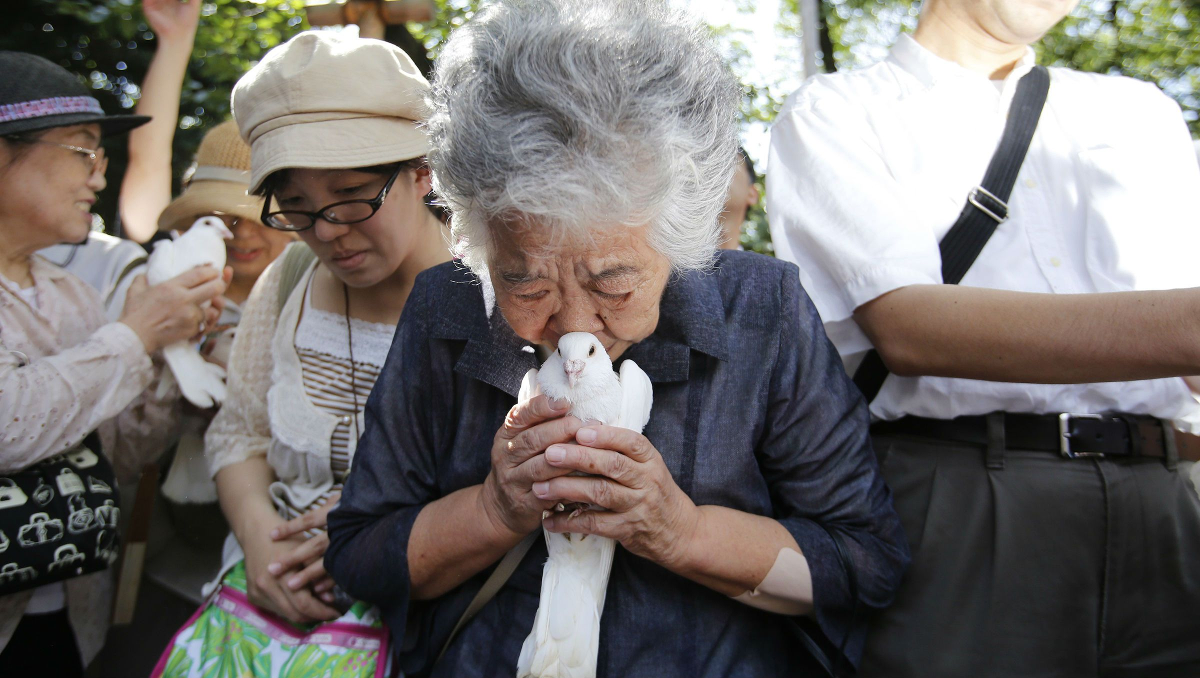 A woman, who lost her father in World War Two, holds a dove before releasing it as she prays for the war dead at the Yasukuni Shrine in Tokyo.