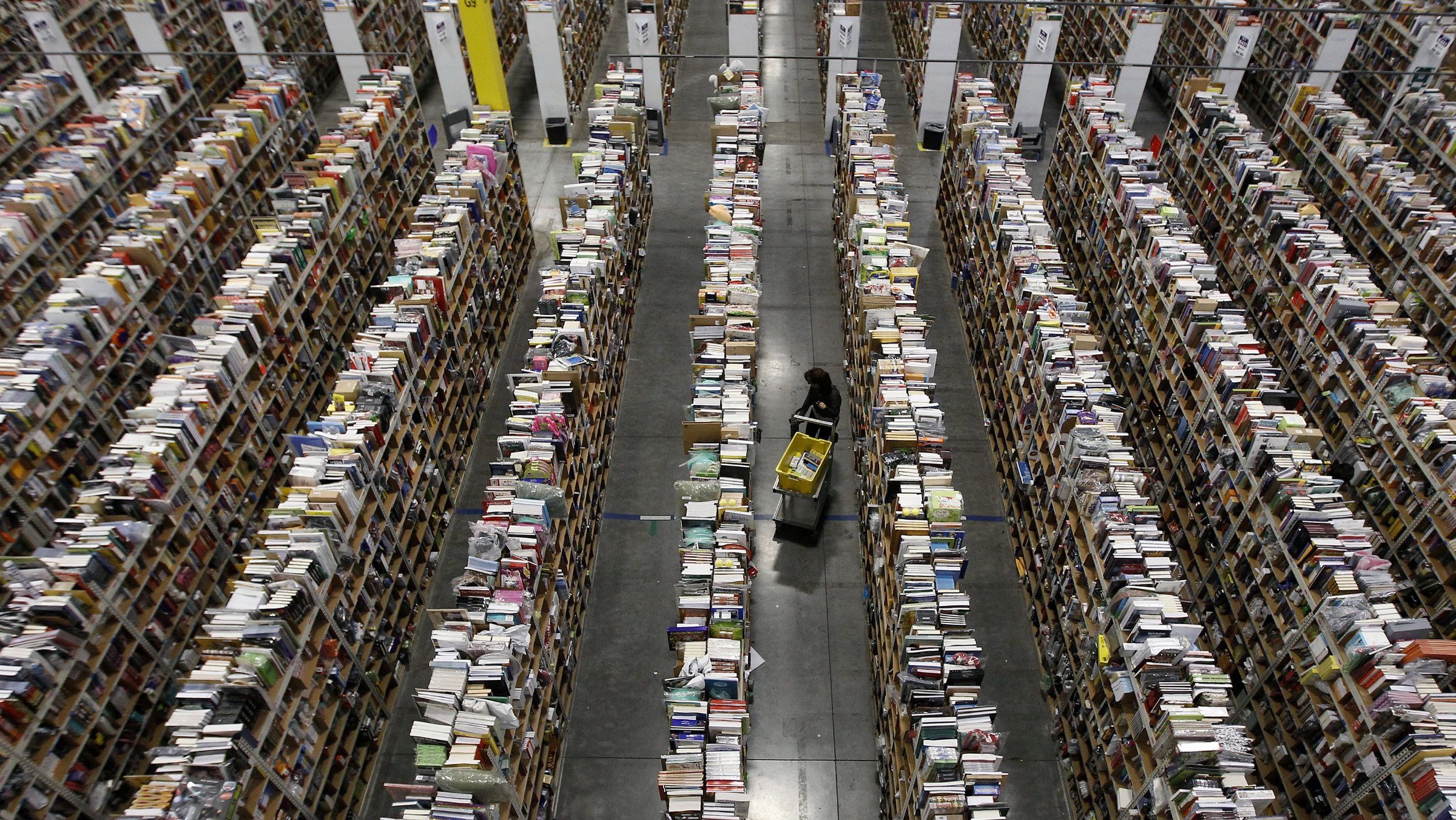 A worker gathers items for delivery from the warehouse floor at Amazon's distribution center in Phoenix, Arizona