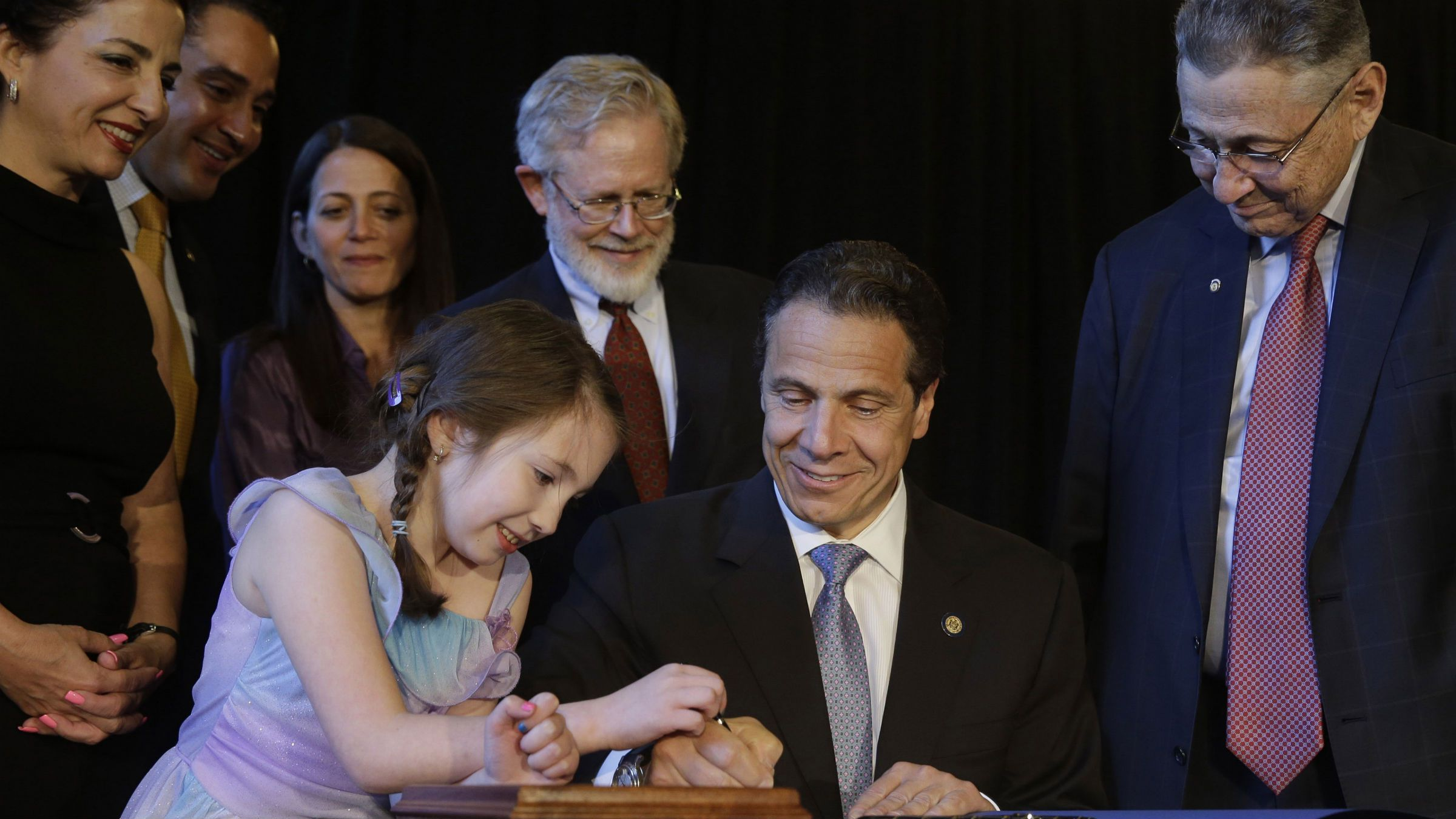New York Governor Andrew Cuomo, second from right, gets some help from Amanda Houser, 10, while signing a ceremonial bill to establish a medical marijuana program in New York, Monday, July 7, 2014.