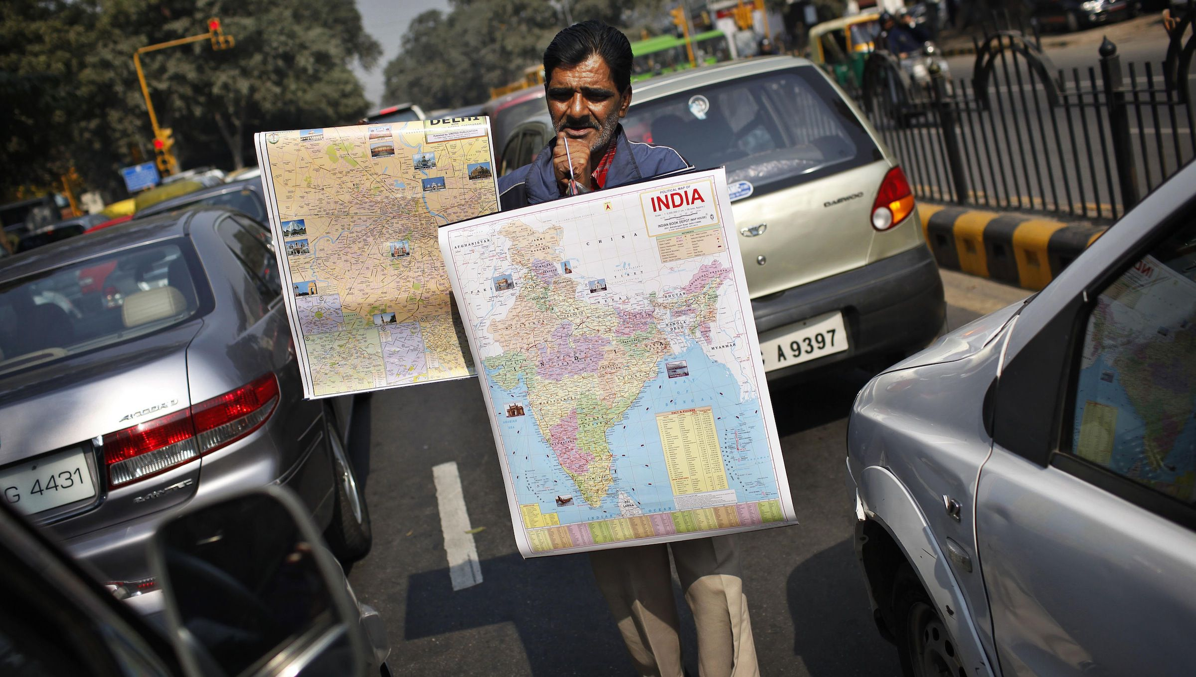 An Indian street vendor tries to sell maps of India and the city of New Delhi in a traffic jam near Connaught Place in New Delhi, India, Friday, Jan. 29, 2010. (AP Photo/Kevin Frayer)