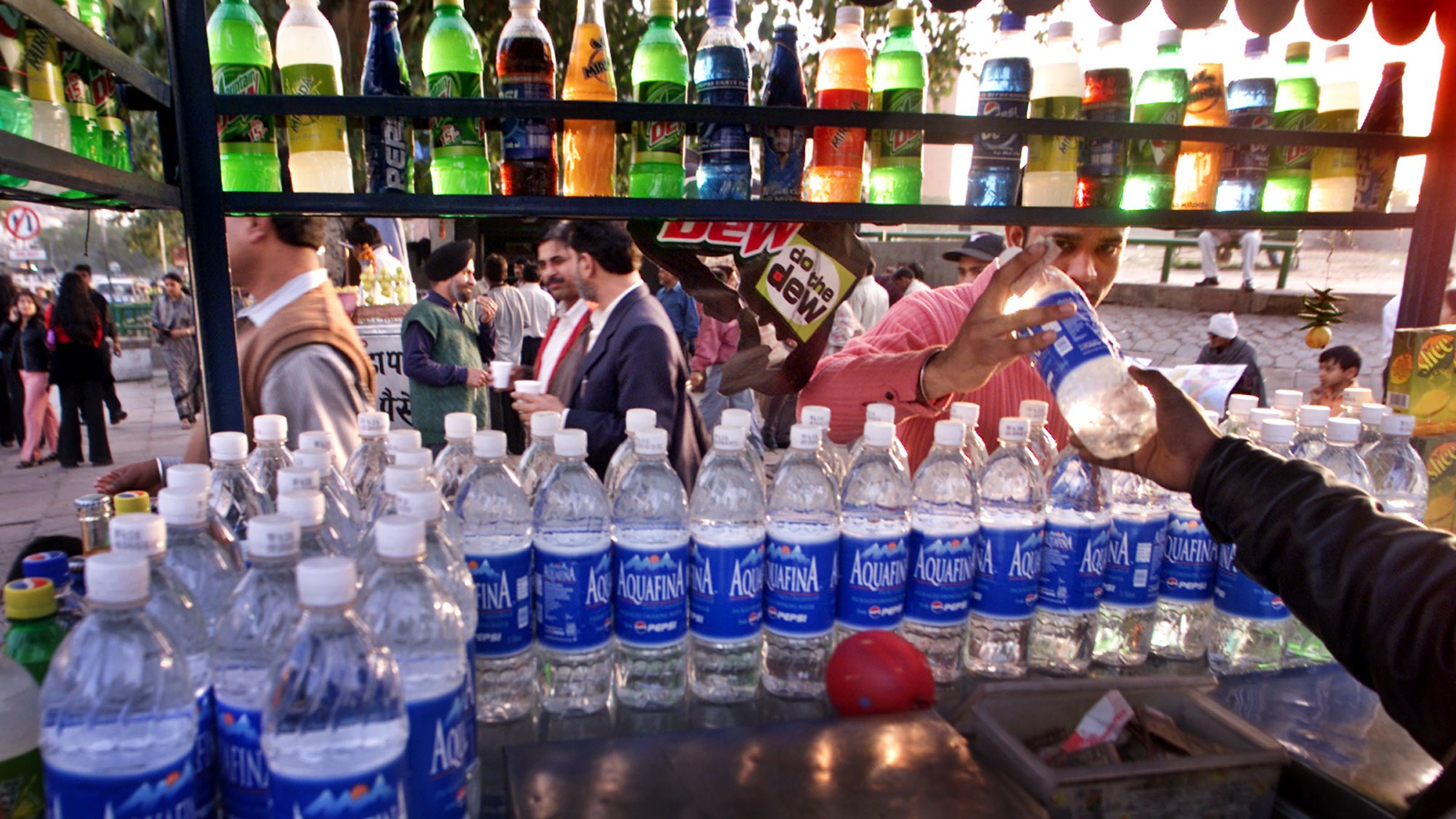 "A customer, right, purchases a bottle of Pepsi's ""Aquafina"" bottled water from a roadside vendor in New Delhi, India, Thursday, Feb. 20, 2003. Indian branches of multinational companies like Pepsi and Coca-Cola have been issued warnings as part of a major crackdown against companies ignoring government's hygiene norms, after high levels of pesticide were found in samples of popular brands of bottled water. (AP Photo/Gurinder Osan)"