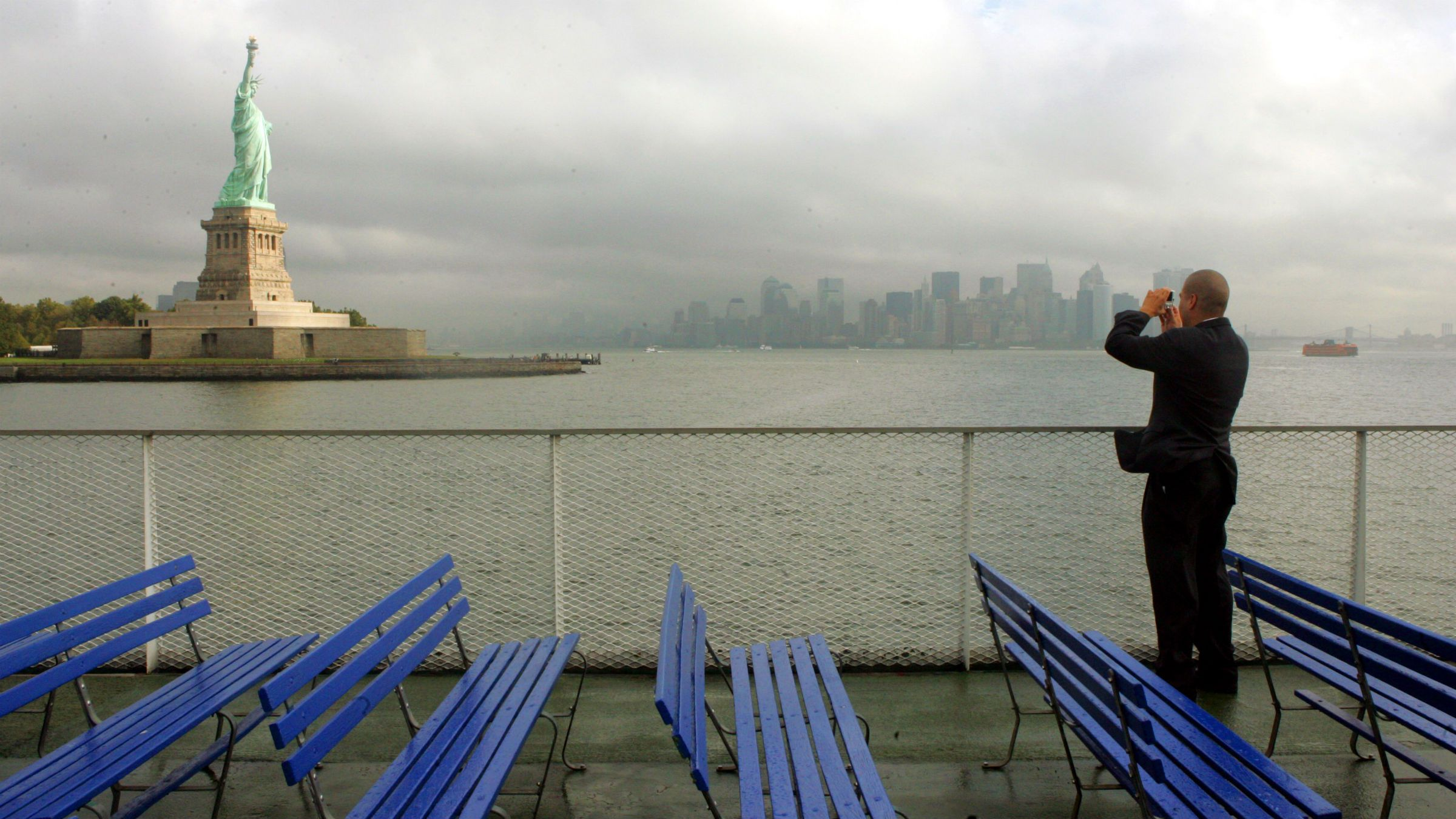 Aldo Abanto, originally from Peru, photographs the Statue of Liberty and the Manhattan skyline while on the way to a ceremony on Ellis Island where he will be taking the Oath of Allegiance and become a U.S. citizen, Sept. 16, 2005 in New York. In celebration of National Citizenship Day, 105 New York residents from 45 countries will take the Oath of Allegiance and become U.S. citizens during a special ceremony at the Registry Room on Ellis Island. (AP Photo/Mary Altaffer)