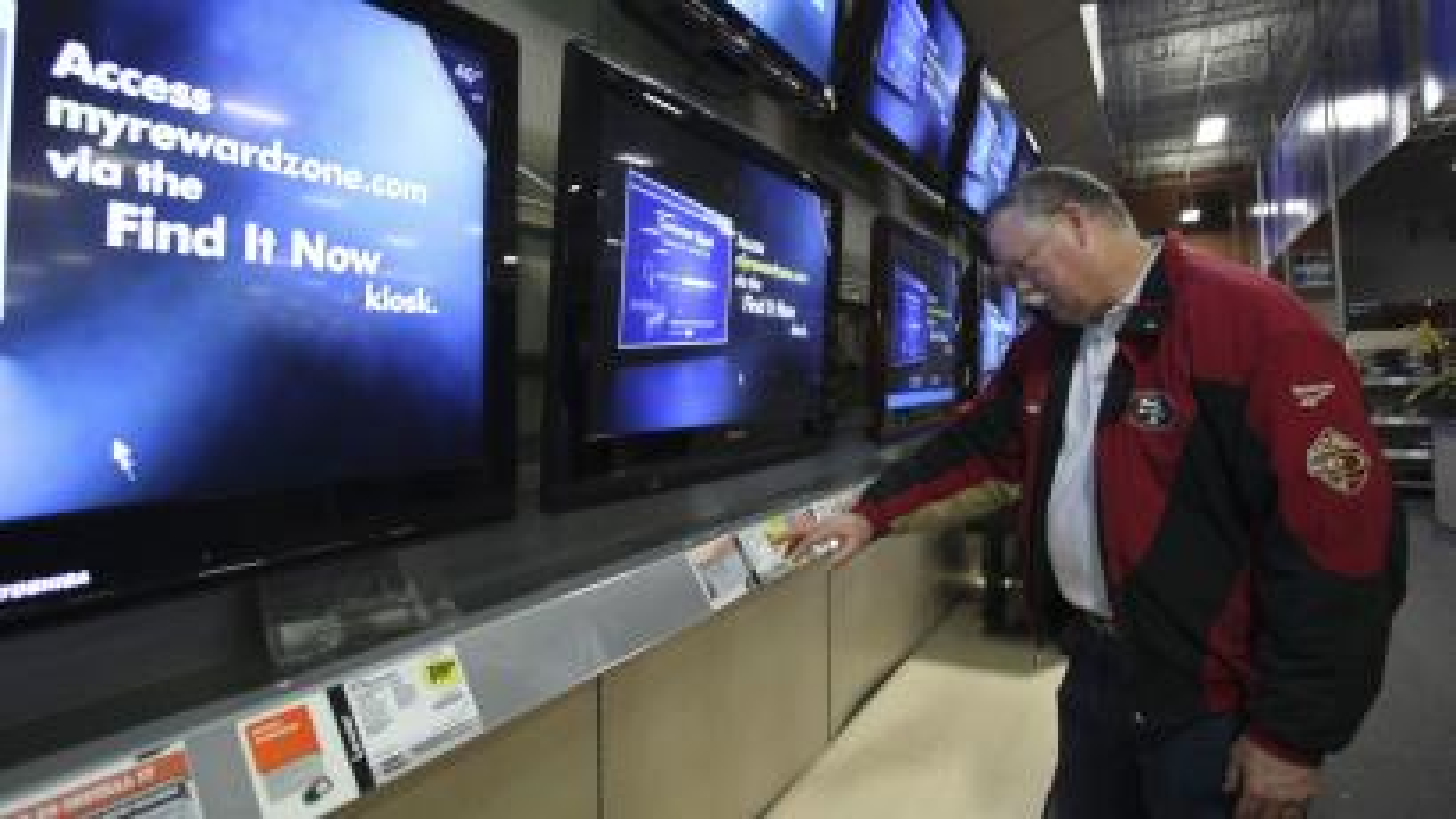 A man looks at TV screens
