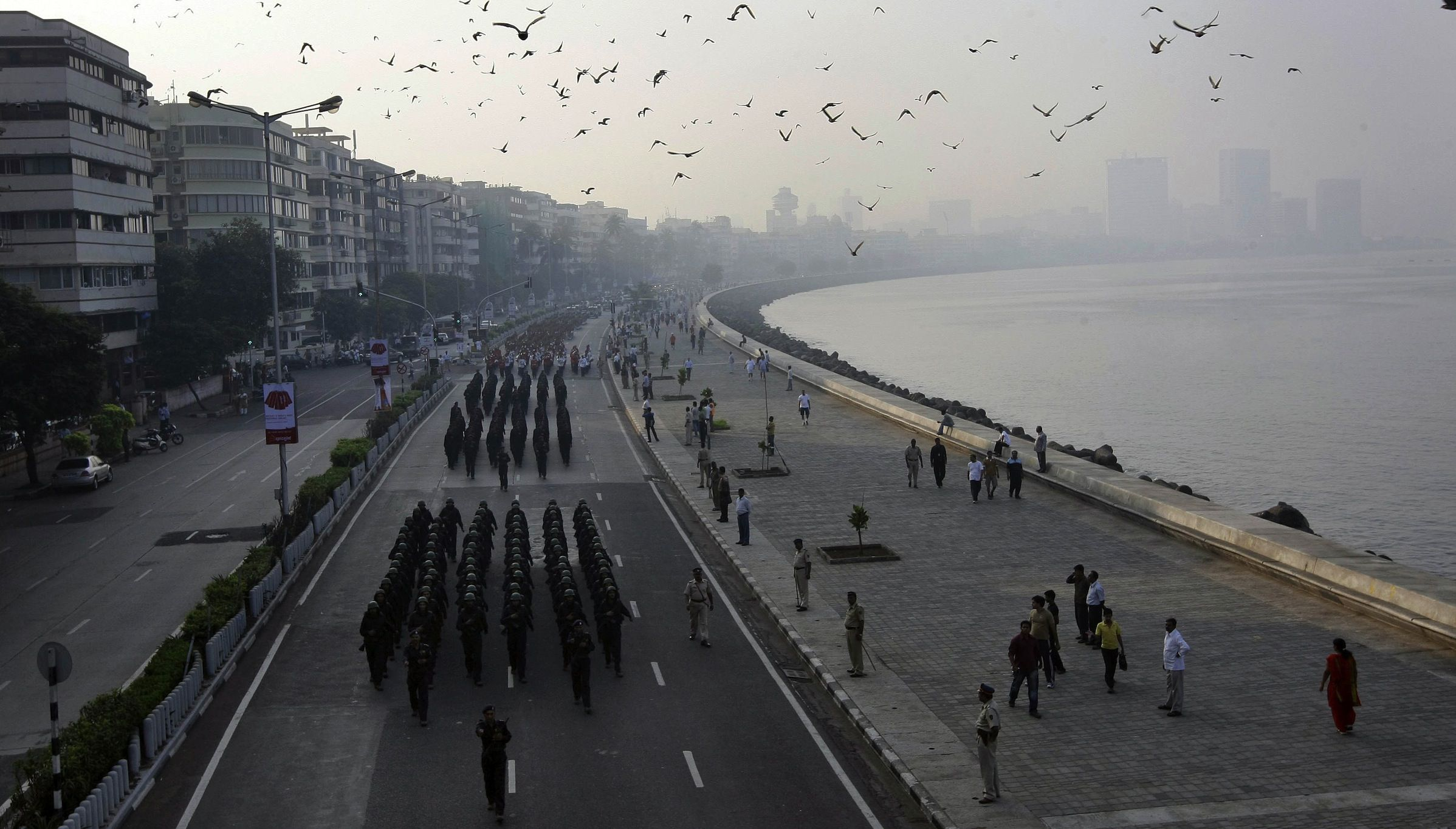 Police officers march in a parade along the seafront at Marine Drive, marking the first anniversary of the terror attack in Mumbai, India, Thursday, Nov. 26, 2009. A police parade bristling with new hardware and armored tanks, a mournful candlelight vigil and a blood donation drive brought Mumbai residents together Thursday as they remembered the city's worst terror attack a year ago that left 166 people dead. (AP Photo/Rajanish Kakade)