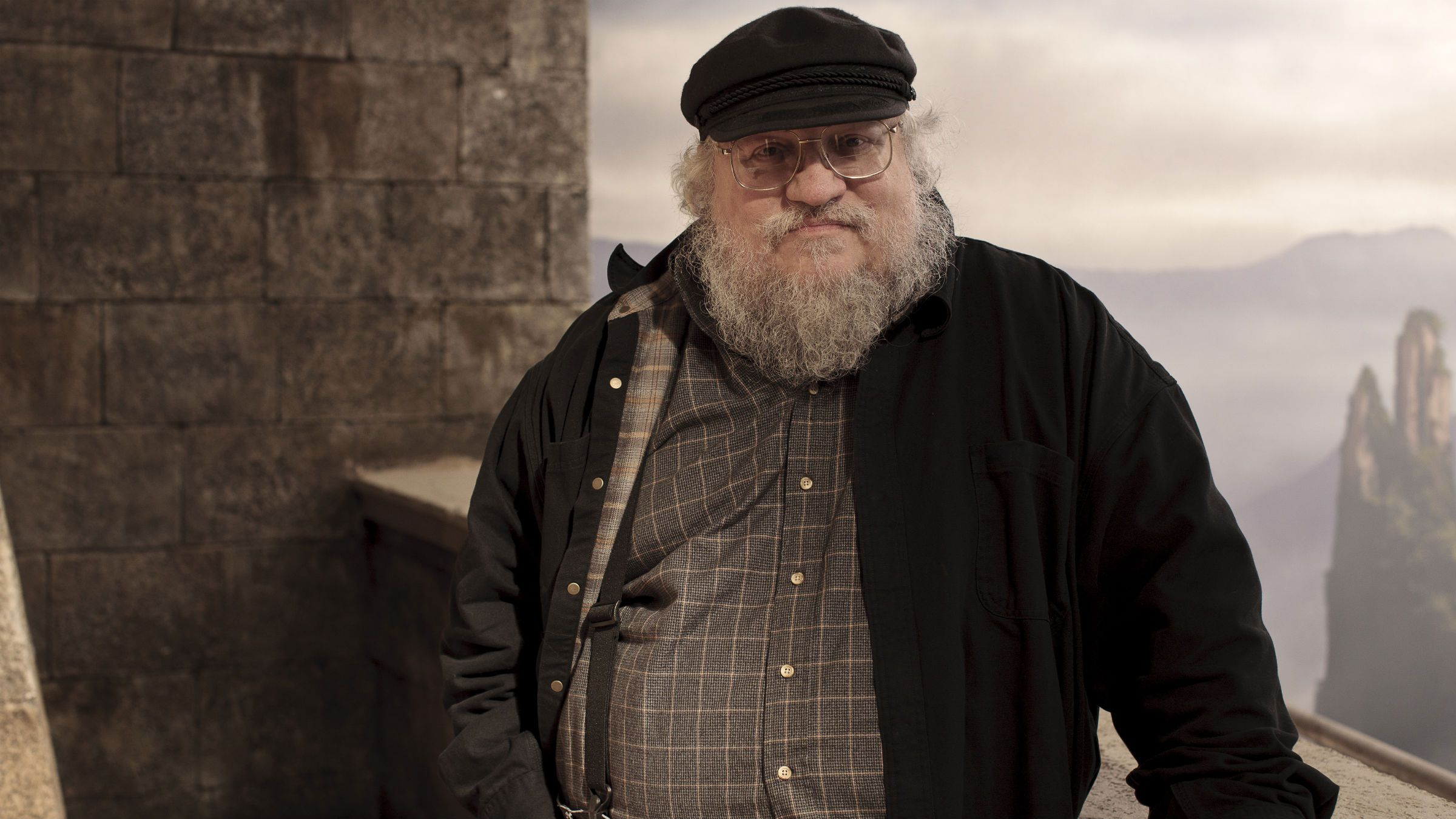 """In this publicity image released by HBO, author George R.R. Martin whose novel series have been adapted into the HBO series """"Game of Thrones,"""" is shown on the set. (AP Photo/HBO, Nick Briggs )"""