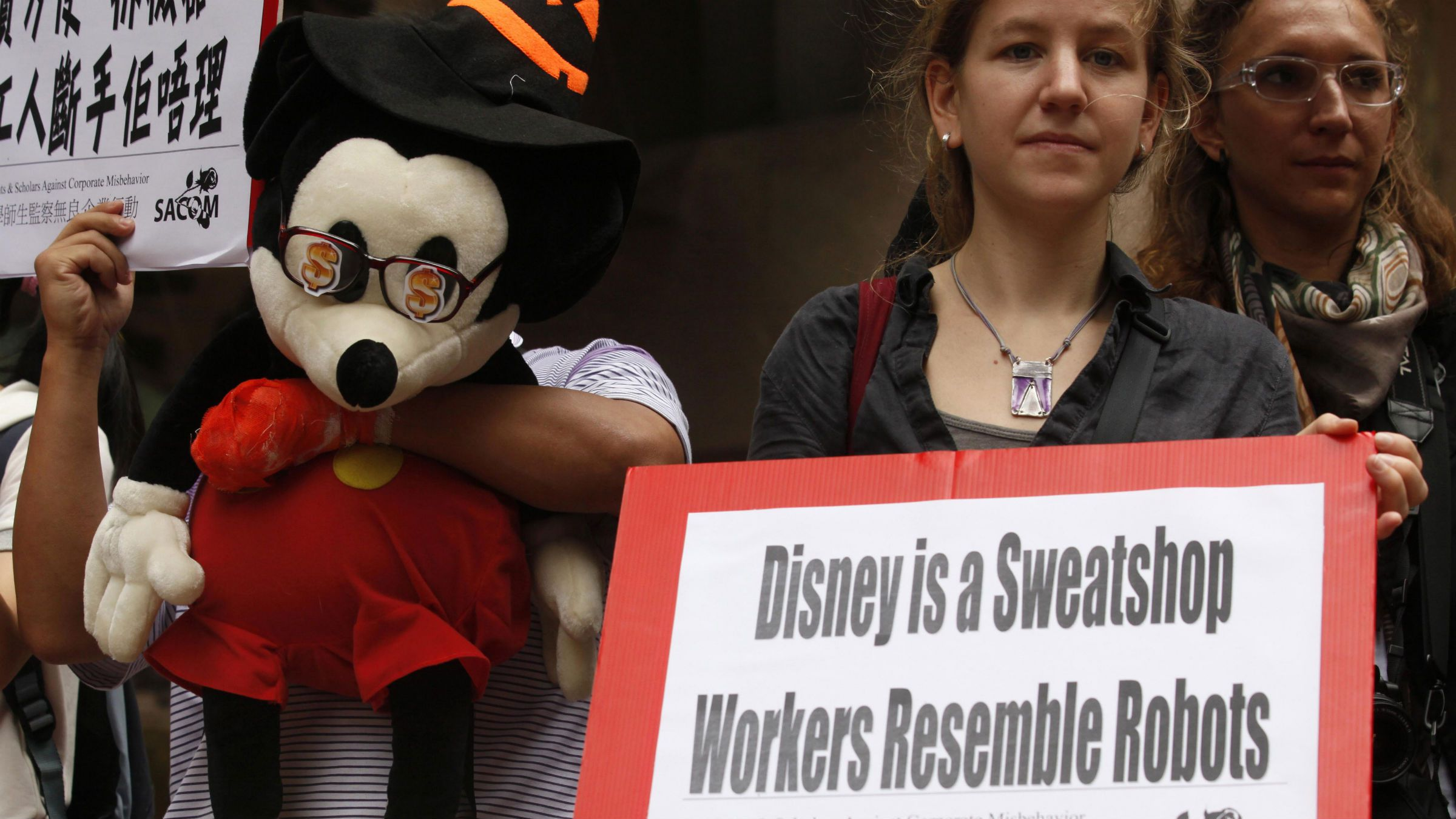 A protester from Students and Scholars Against Corporate Misbehavior holds a Mickey Mouse wearing glasses with dollar signs as they demonstrate near the Walt Disney Co. (Asia Pacific) Ltd. Office in Hong Kong Friday, Oct. 22, 2010. The protesters were demanding the Disney toy suppliers pay raise and better labor condition in China. (AP Photo/Kin Cheung)
