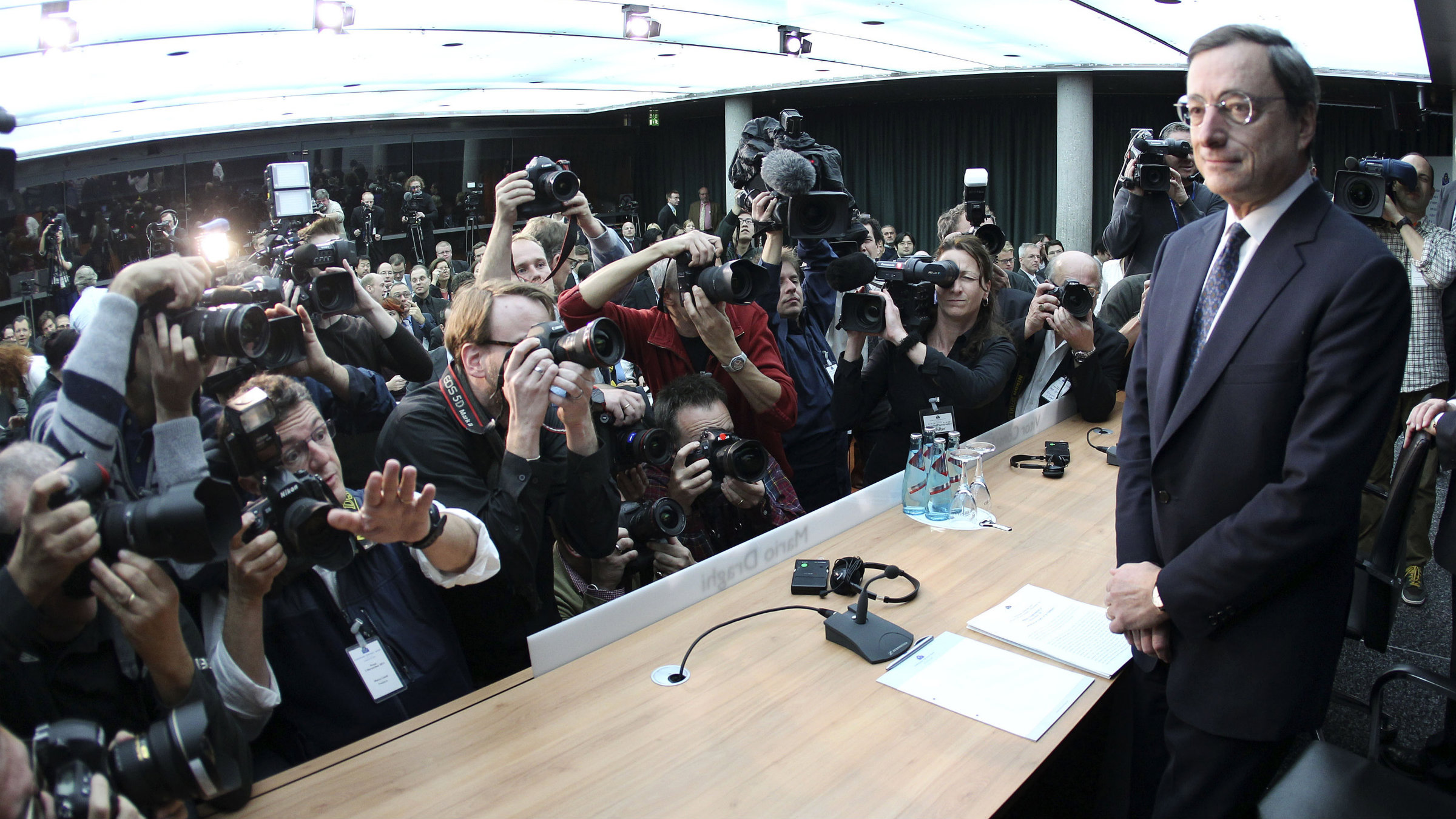 Mario Draghi, President of the European Central Bank, is surrounded by photographers prior to a press conference in Frankfurt.