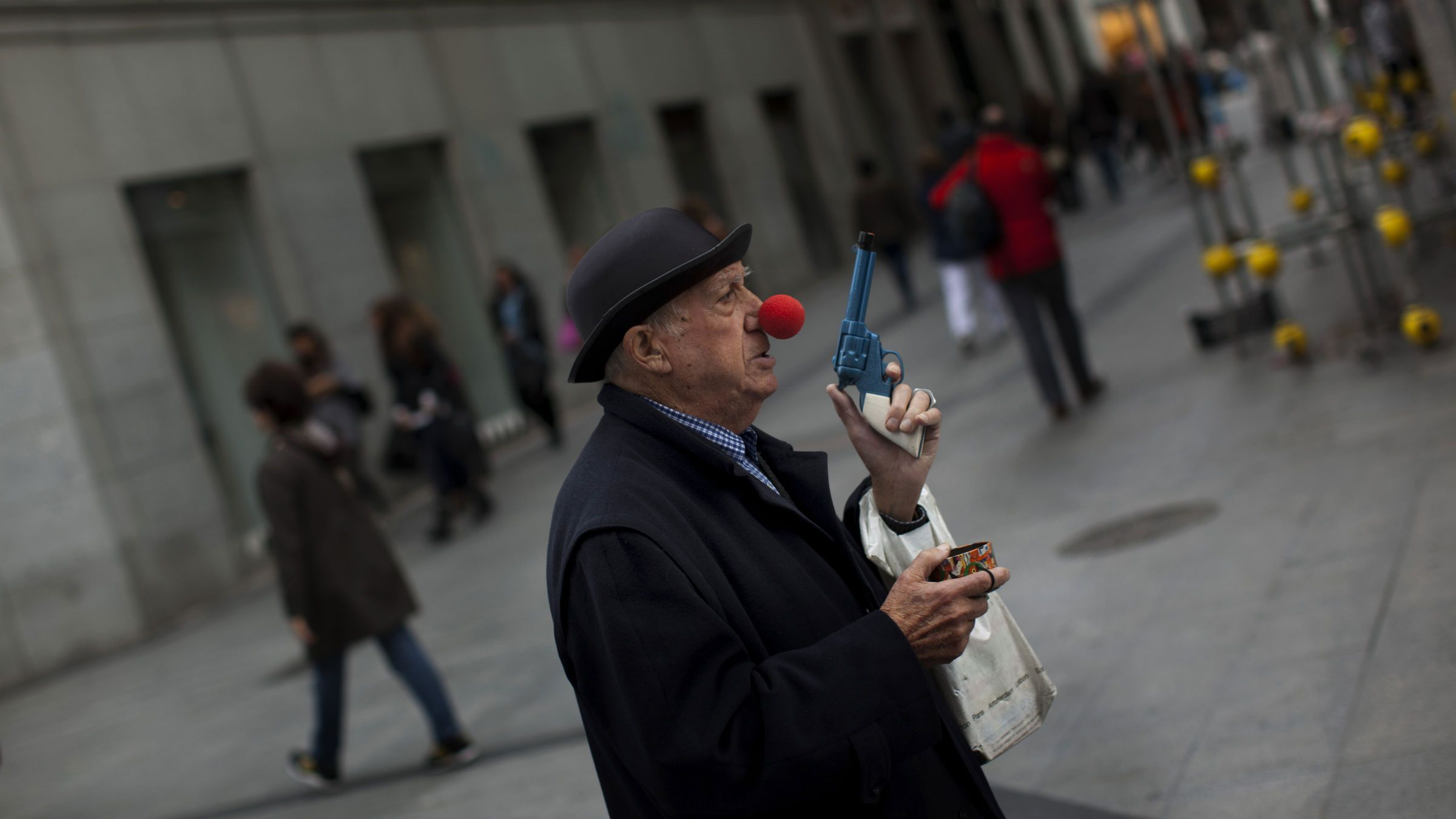 Old man wears a clown nose while begging