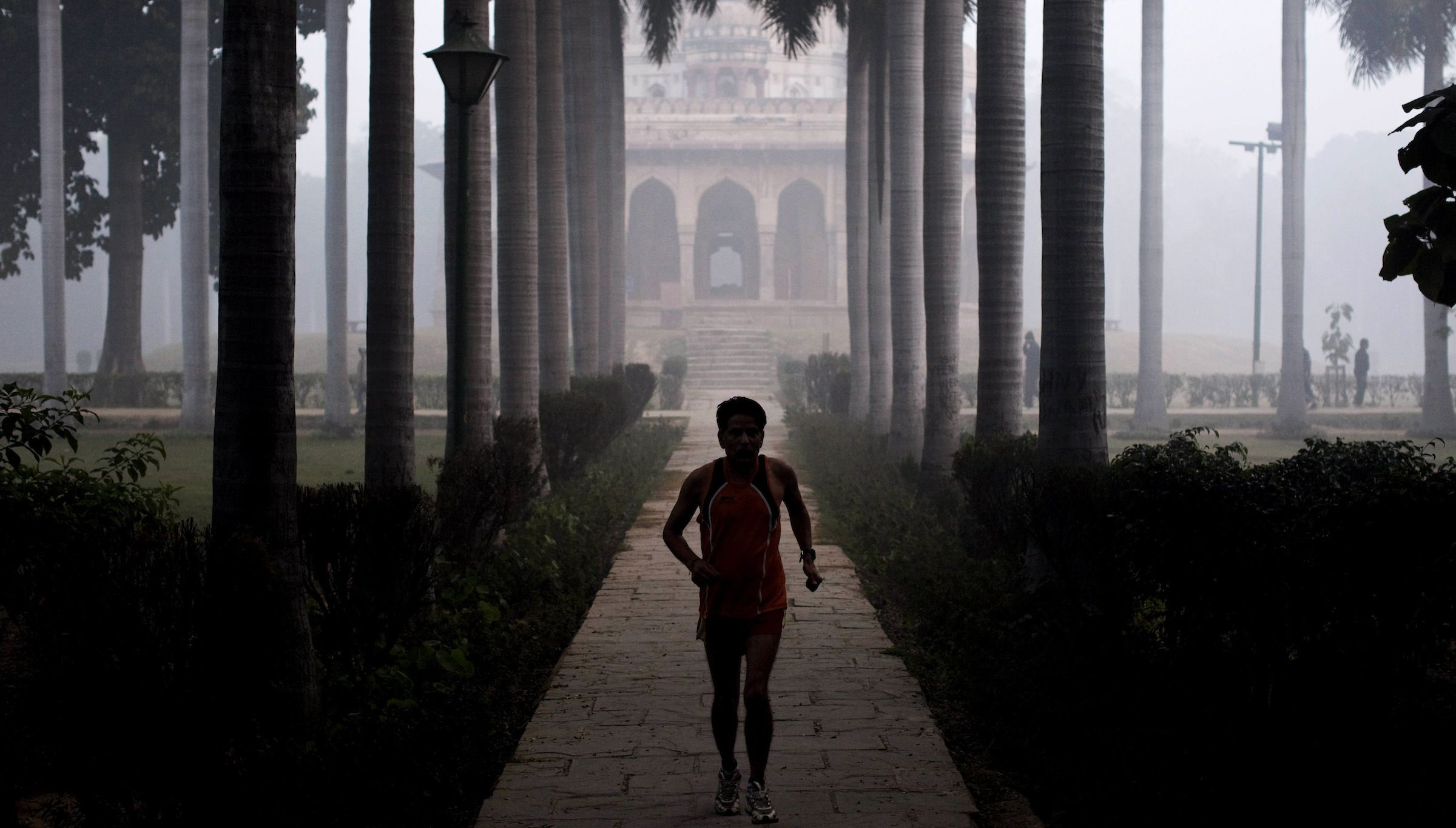 An Indian man runs in the fog at Lodhi Gardens in New Delhi, India, Friday, Dec. 23, 2011. Though India is famous for its brutally hot summers, temperatures fall sharply for a few weeks in December and January. (AP Photo/Kevin Frayer)