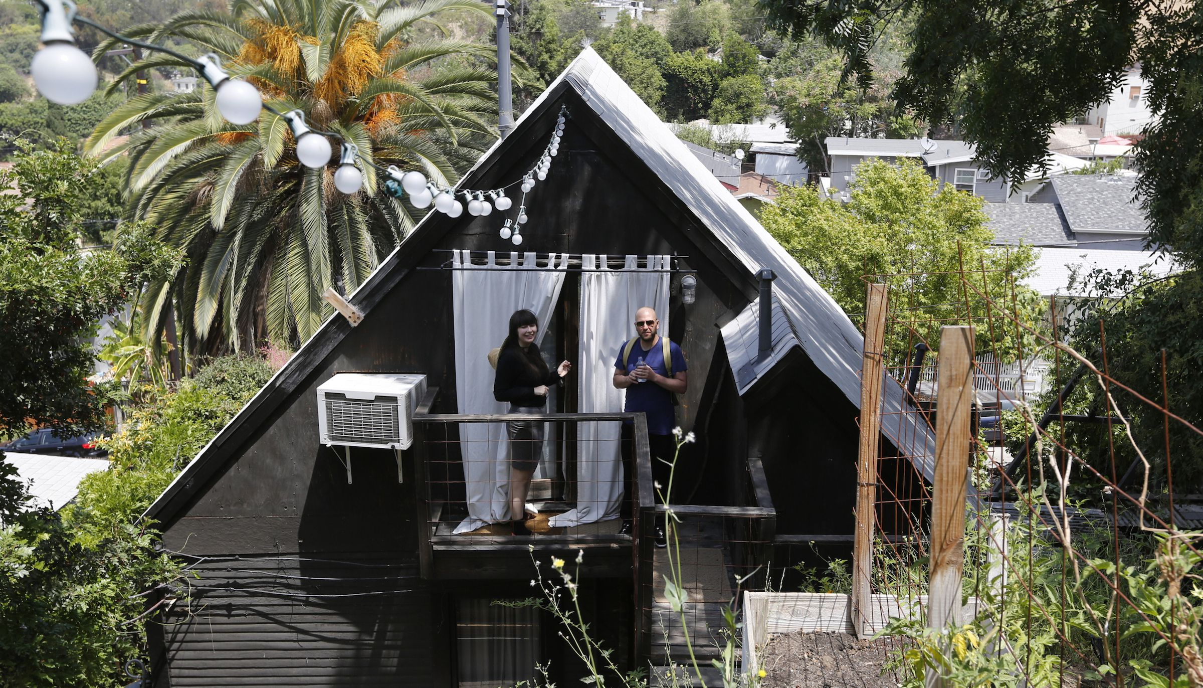In this Monday, May 19, 2014 photo, Airbnb guests Camille Smithwick and James Green from Manchester, U.K., pose for photos at an Airbnb property owned by ceramist Jonathan Entler in the Echo Park area of Los Angeles. Deeper savings can be had through sites such as Airbnb that arrange for people to rent out rooms, apartments or even couches. The number of listed accommodations has soared since Airbnb's founding in 2008 to 550,000 _ not far below Hilton's 685,000 rooms worldwide. (AP Photo/Damian Dovarganes)