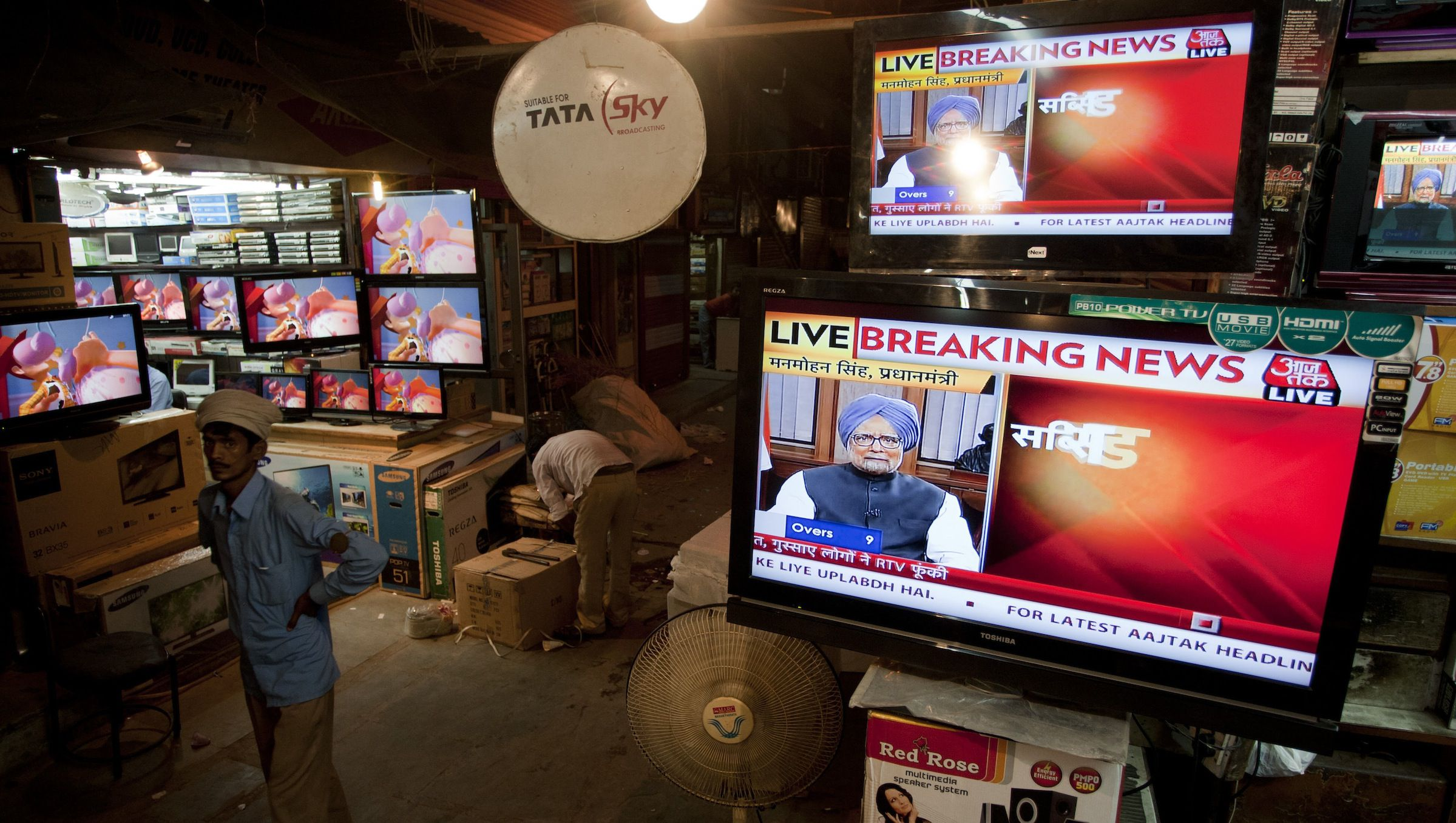 An Indian laborer walks past televisions showing Prime Minister Manmohan Singh's address to the nation, at a television store in New Delhi, India, Friday, Sept. 21, 2012. Singh's address to the nation came after the Trinamool Congress party pulled out of the ruling coalition protesting the decision to allow foreign retail chains to come into the country.  (AP Photo/Tsering Topgyal)