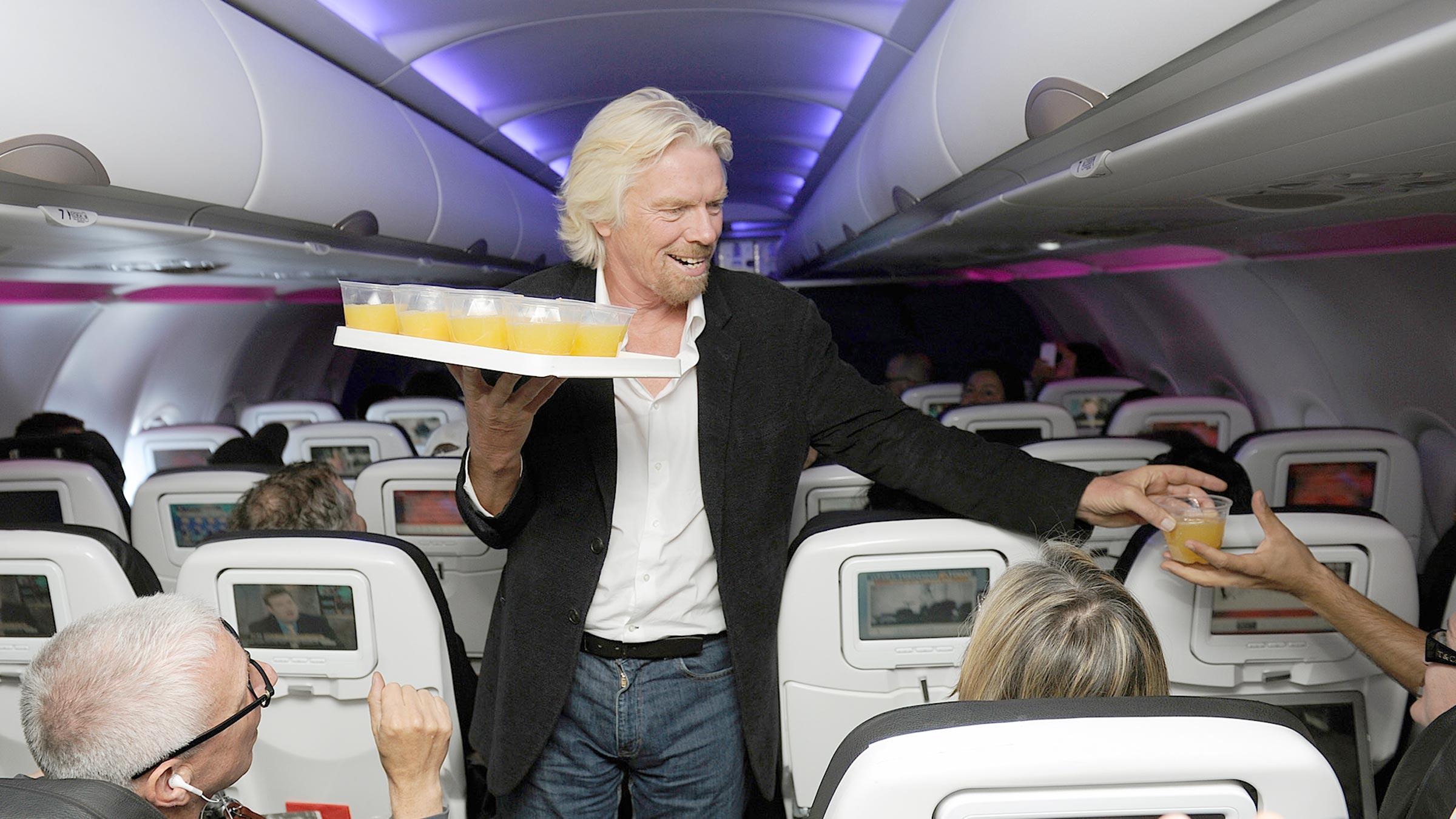 Richard Branson hands out orange juice.