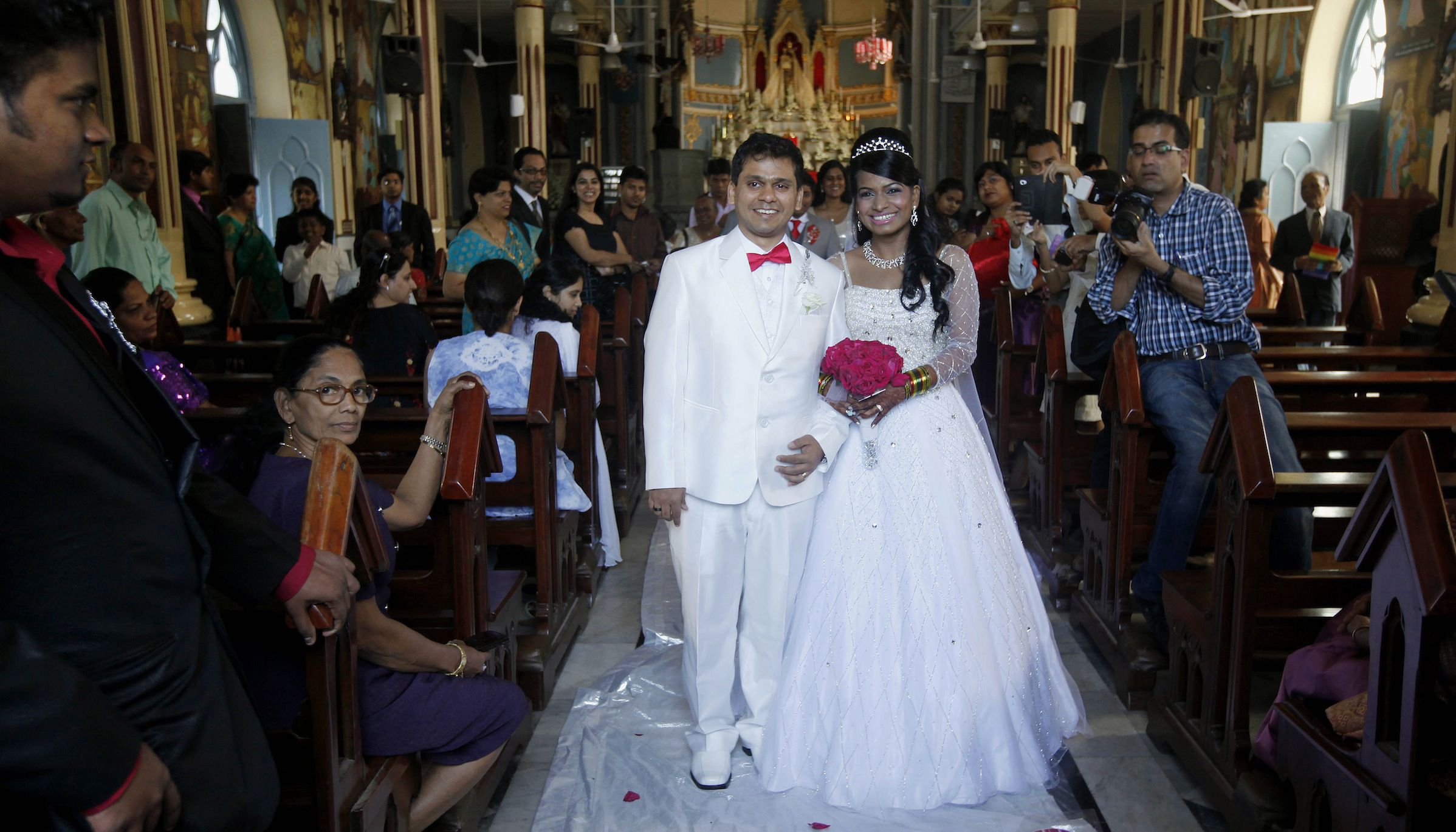 Newlywed Indian couple Brandon Pereira and Emilia D'Silva, right, pose after being married at a church in Mumbai, India, Wednesday, Dec. 12, 2012. The couple were engaged on 10/10/10, registered a legal marriage on 11/11/11 and had their official ceremony today on 12/12/12, a date seen as auspicious by many astrologers and that won't happen again for almost 100 years.  (AP Photo/Rajanish Kakade)