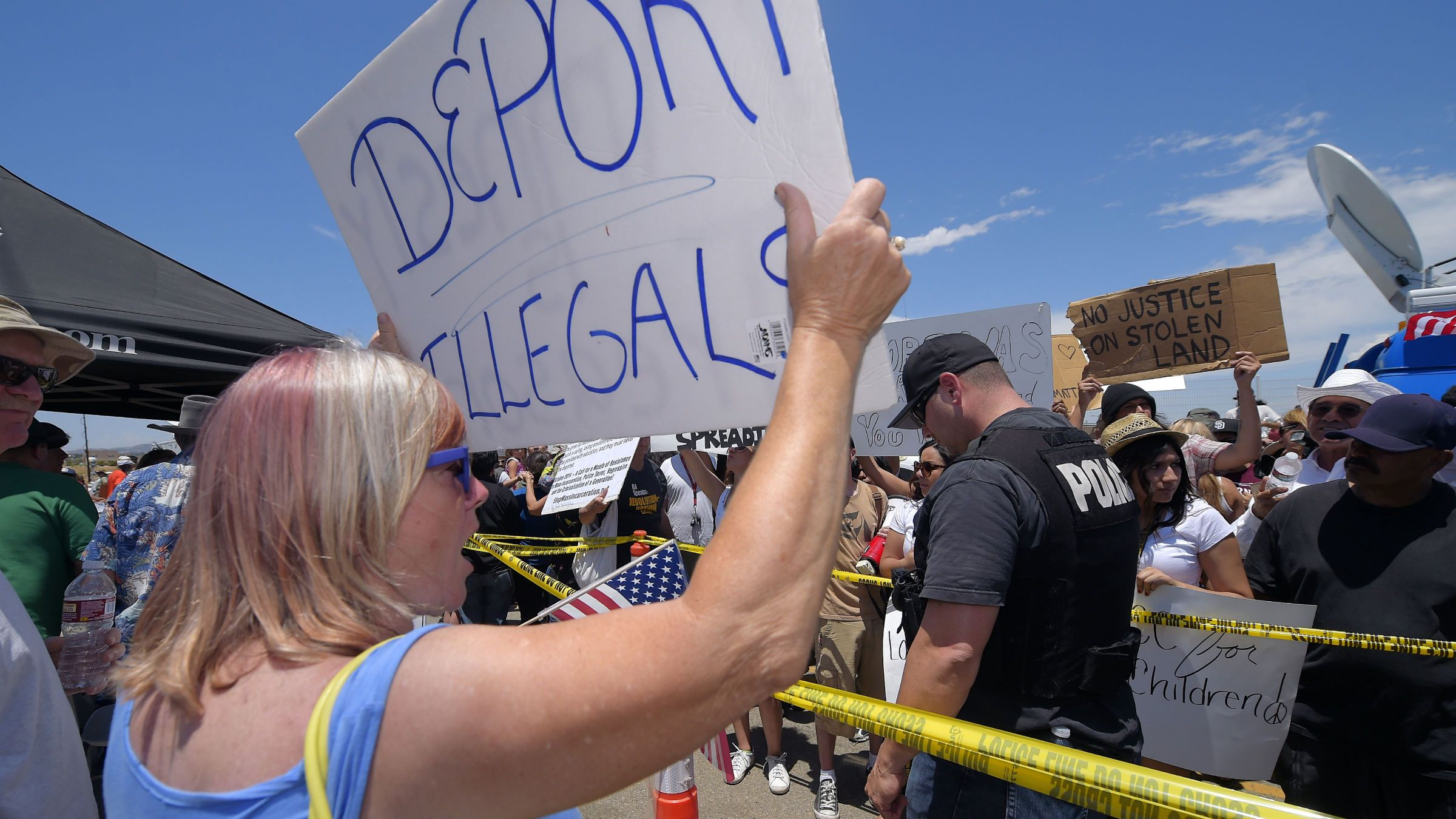A demonstrator that opposes illegal immigration, left, shouts at immigration supporters, Friday, July 4, 2014, outside a U.S. Border Patrol station in Murrieta, Calif. Demonstrators on both sides of the immigration debate had gathered where the agency was foiled earlier this week in an attempt to bus in and process some of the immigrants who have flooded the Texas border with Mexico. (AP Photo/Mark J. Terrill)