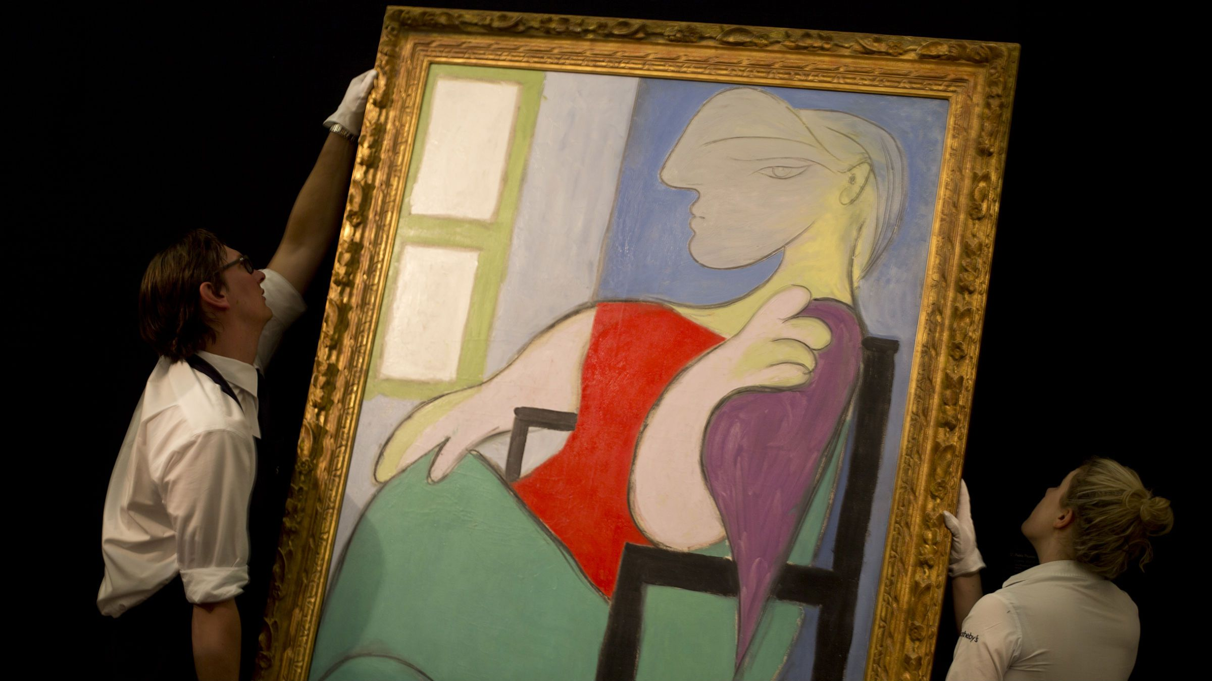 """Two Sotheby's employees adjust a painting by Pablo Picasso entitled """"Femme assise pres d'une fenetre"""" 1932, at Sotheby's auction house during a press preview in London, Thursday, Jan. 31, 2013. The work is estimated to sell for some 25-35 million pounds (US$ 39.5-55 million, euro 29.1-40.8 million) when sold at auction on Feb. 5, in London. (AP Photo/Alastair Grant)"""