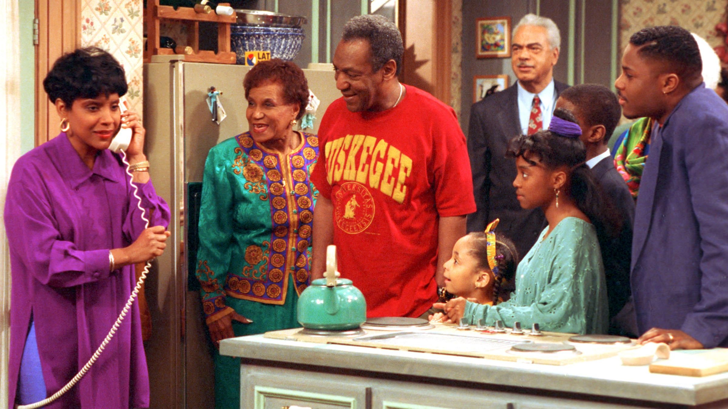 """Phylicia Rashad, as Clair Huxtable, talks on the telephone while Bill Cosby, as Dr. Cliff Huxtable and other cast members of the family sitcom """"The Cosby Show"""" gather around during taping of the final episode in New York City, Friday, March 6, 1992. From left clockwise are, Rashad; Clarice Taylor as Anna Huxtable; Cosby; Earl Hyman as Russel Huxtable; unidentified actor, partially hidden; Malcolm Jamal Warner as Theo; Keshia Knight Pulliam as Rudy; and Raven Symone as Olivia. (AP Photo)"""