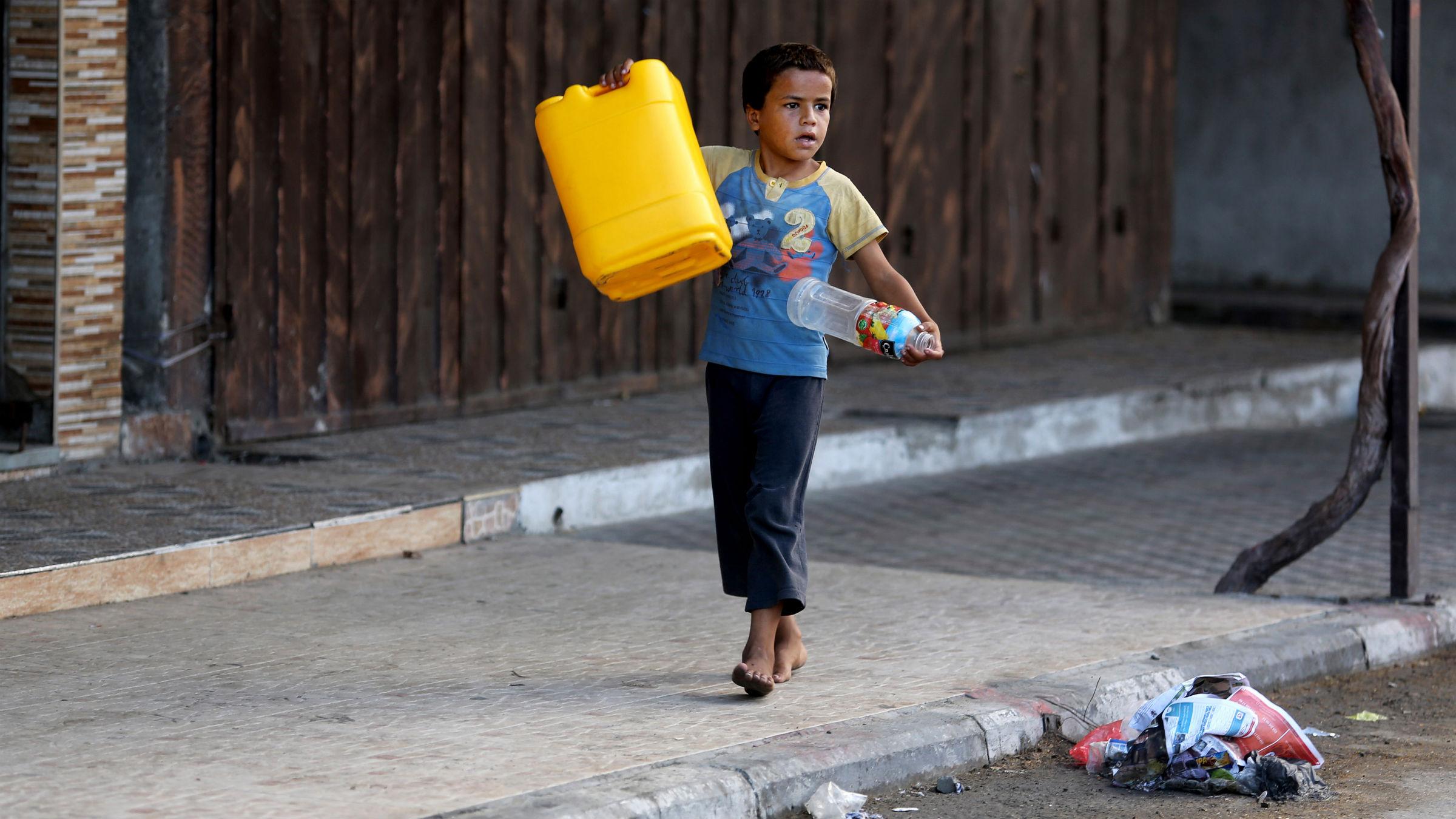 Boy gathering water in Gaza