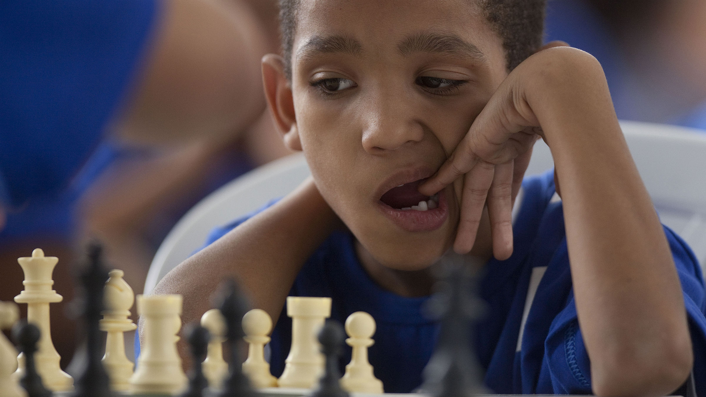 Boy thinks hard while playing chess